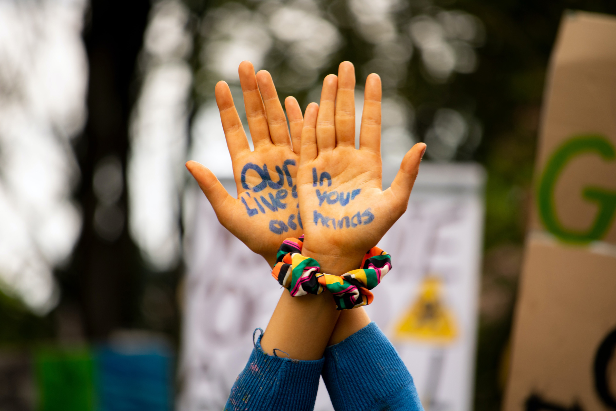 "A pair of hands raised in protest with the words ""Our lives are in your hands"""