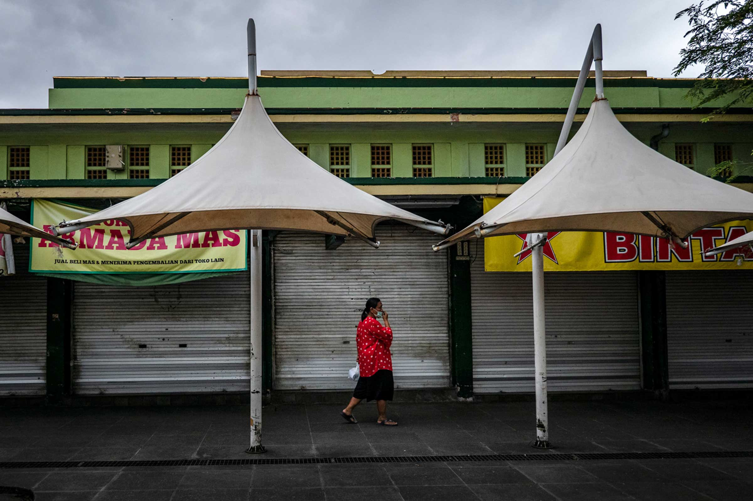 A woman wears a protective mask and walks at the nearly-empty Beringharjo market