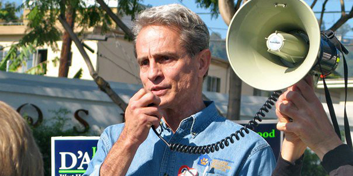 A man with gray hair speaks into a megaphone at a political rally, wearing an anti-fur pin