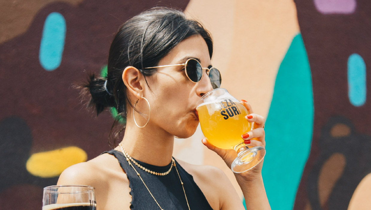 a brownskinned woman of color wearing dark sunglasses holds a glass of beer to her lips