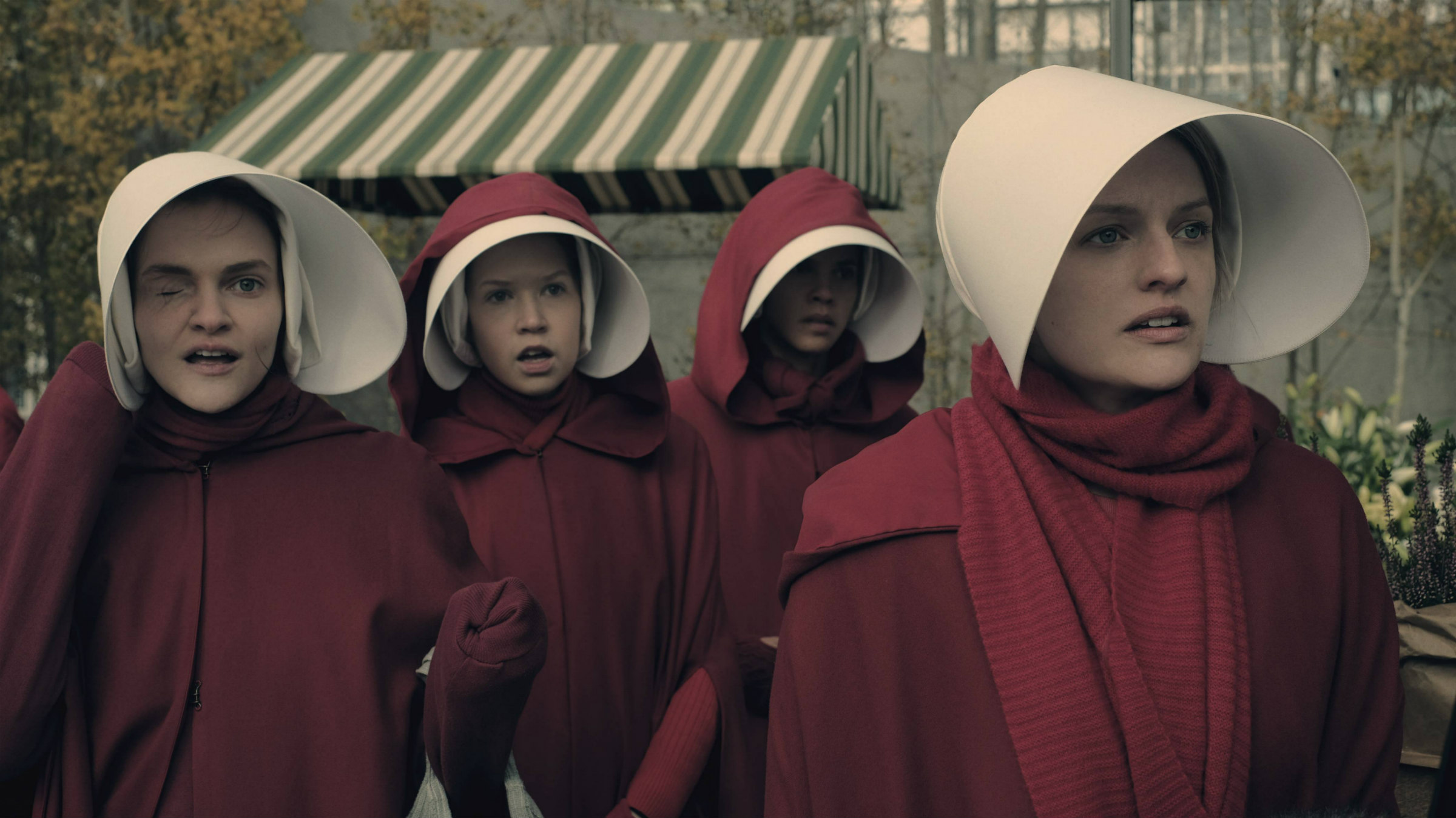 four white women wear red robes with white hats in The Handmaid's Tale