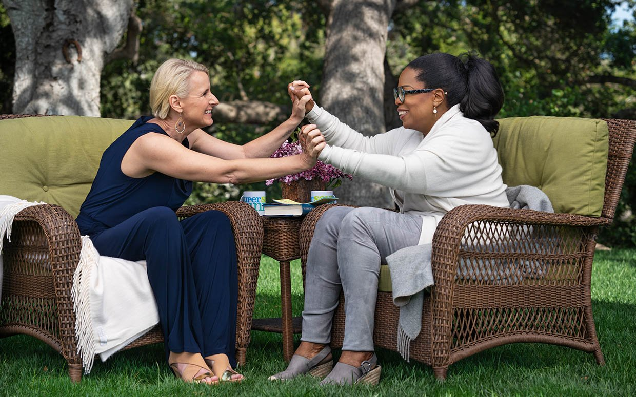 Elizabeth Gilbert, a white woman wearing a navy blue jumpsuit, leans forward and holds hand with and Oprah Winfrey, a Black woman wearing a gray cardigan and jeans