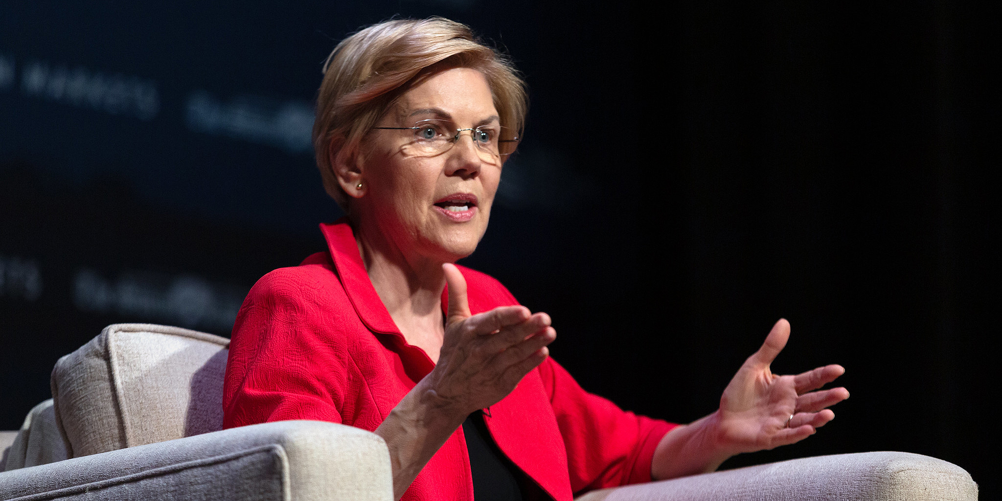 Elizabeth Warren wearing a red blazer, sitting in a beige chair, and holding both hands out as she gestures to the audience she's speaking to