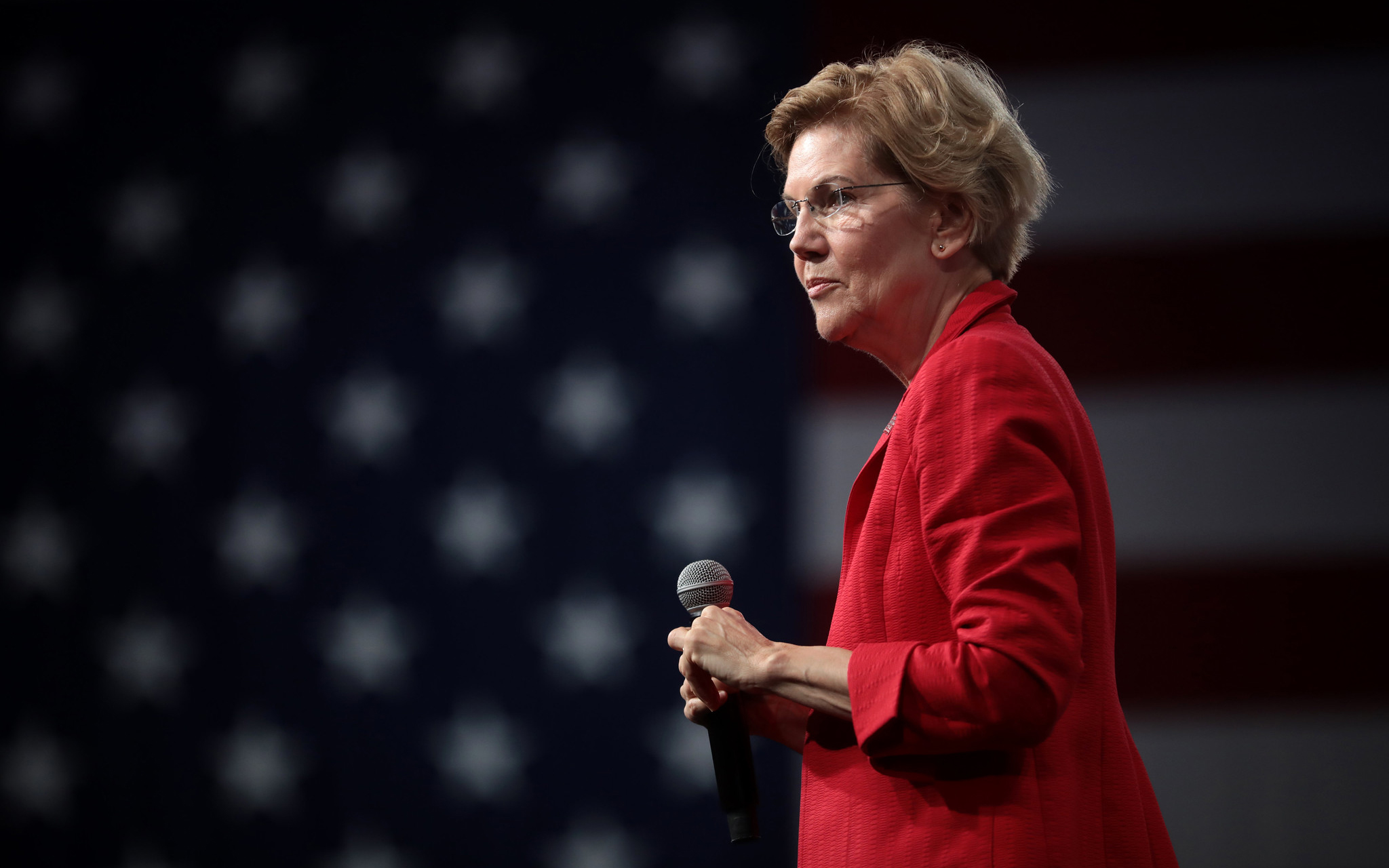 Elizabeth Warren standing on stage with a microphone, wearing a red blazer and an American flag in the background. Her expression is neutral.