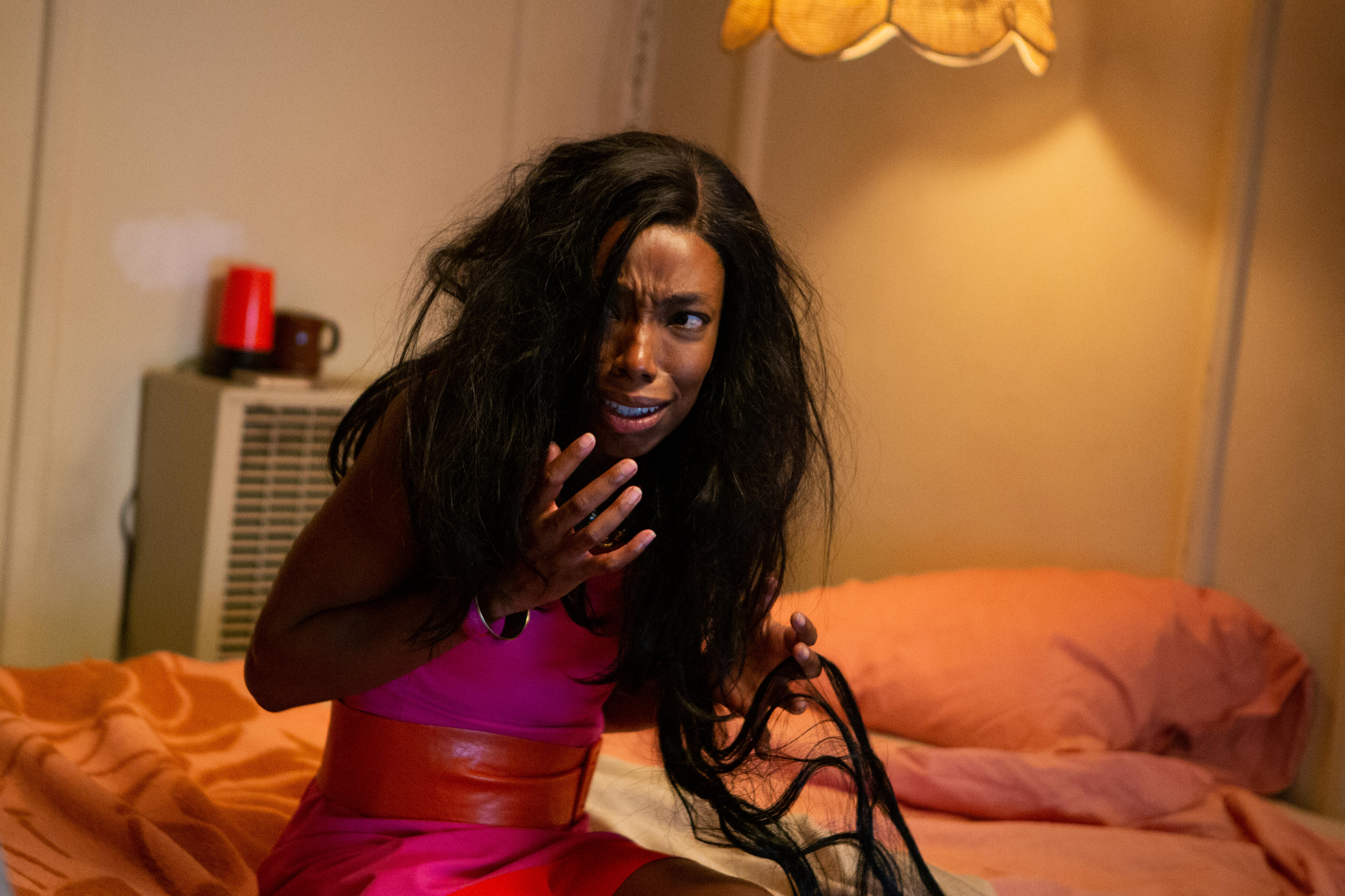 Elle Lorraine plays Anna, a dark-skinned Black woman with long, Black hair, sits horrified on a bed in in Bad Hair