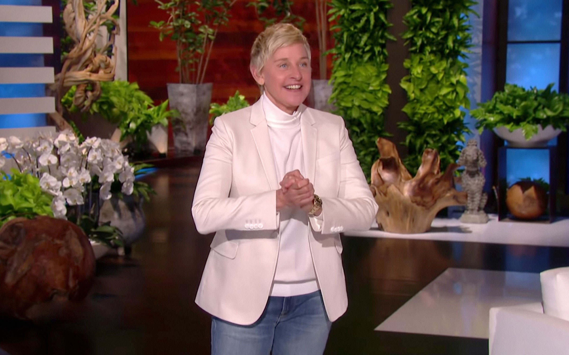 Ellen DeGeneres, a white woman with short blond hair, walks on stage.