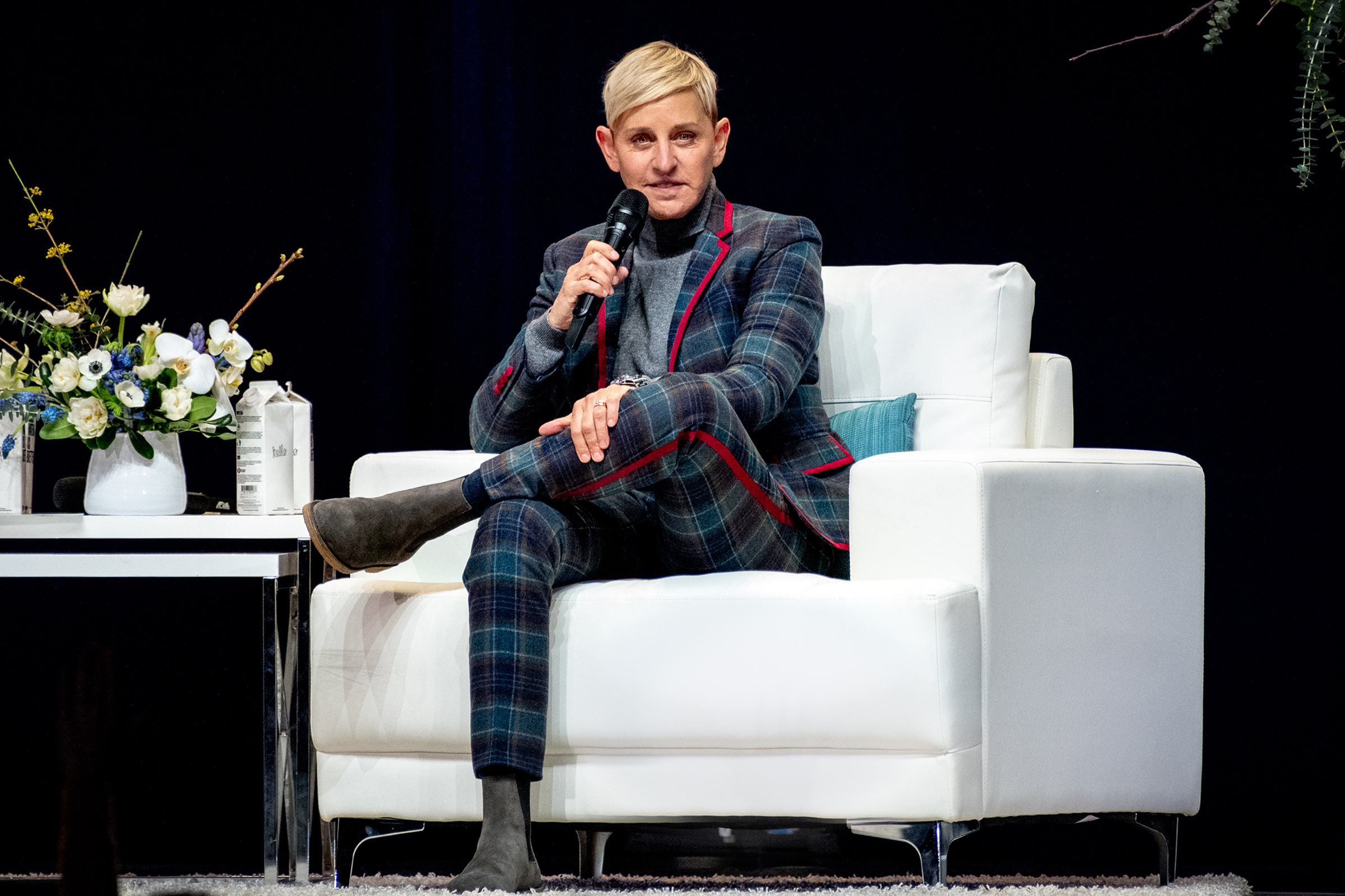 Ellen DeGeneres, a white woman with short blond hair, sits on stage and holds a microphone.