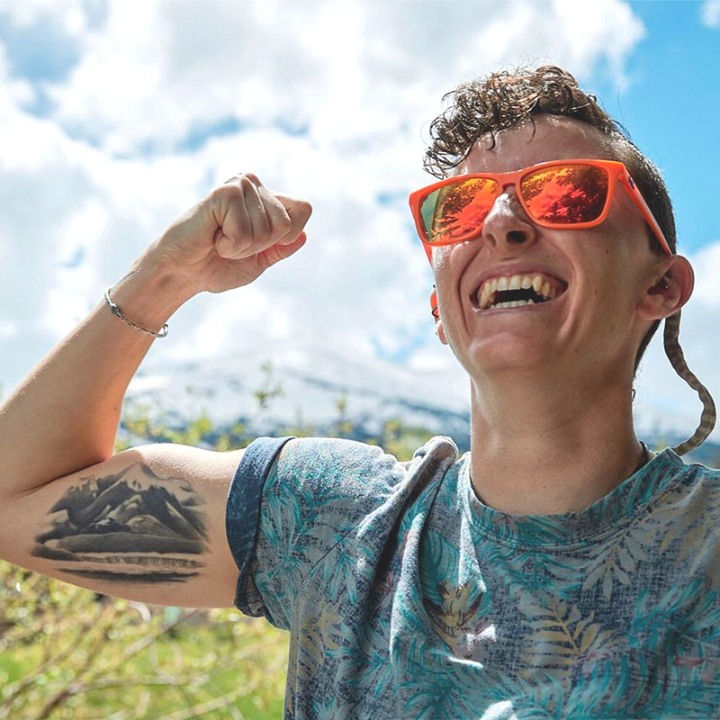 Photo of a white cisgender queer woman with short curly hair wearing orange sunglasses and smiling while flexing her tattooed arm