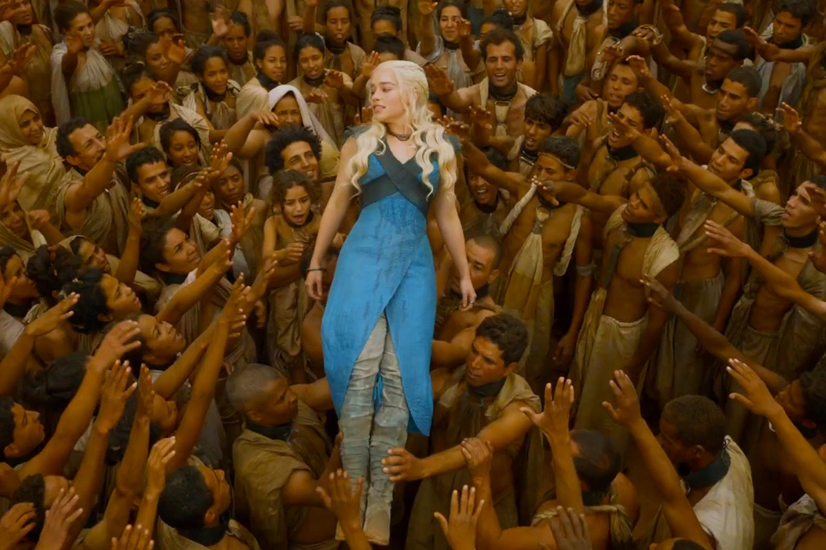 a photo of a white woman with platinum blond hair and a blue dress being held up by a group of Brown people