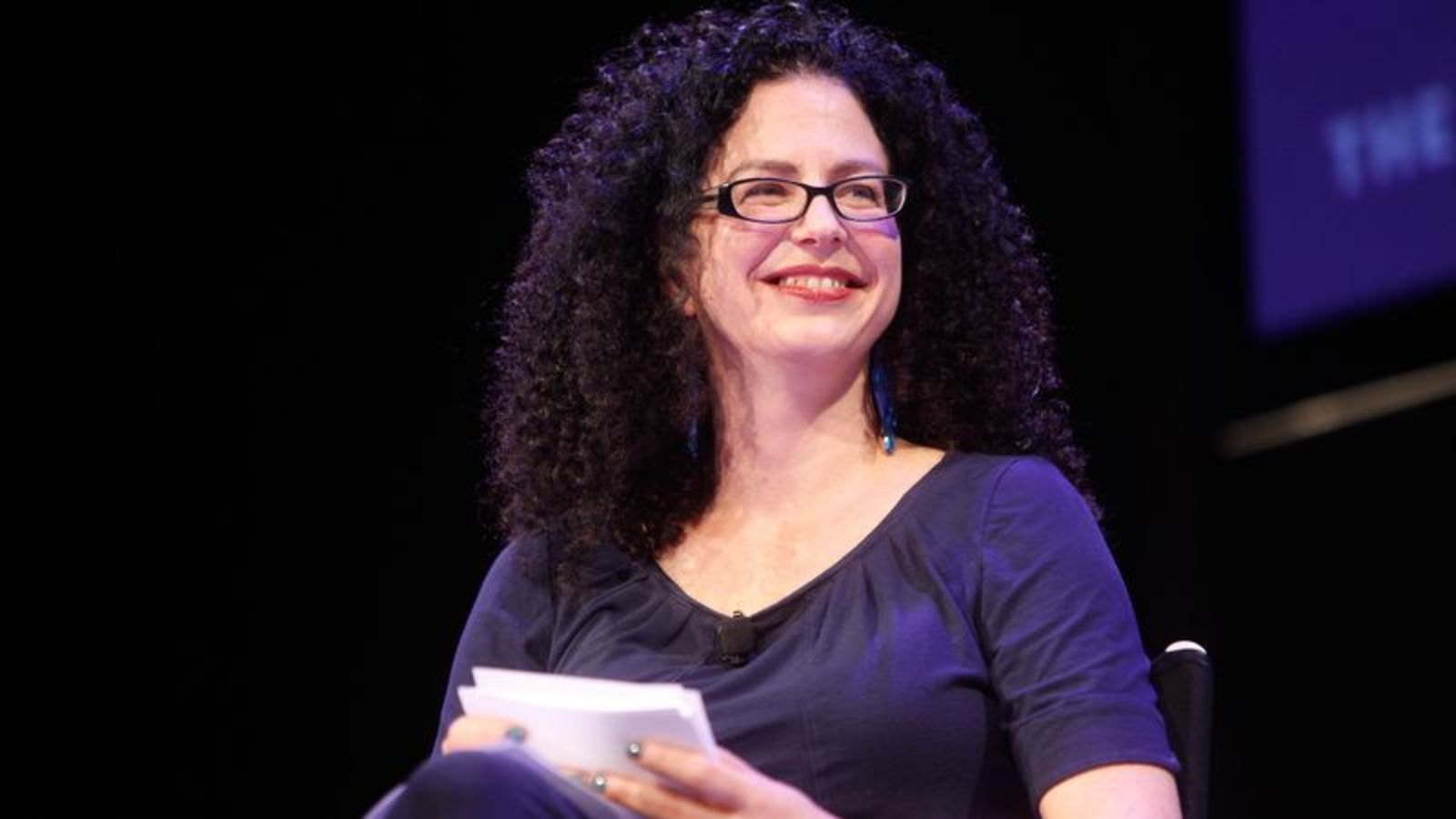 a white woman with glasses with shoulder-length curls sits on a stage