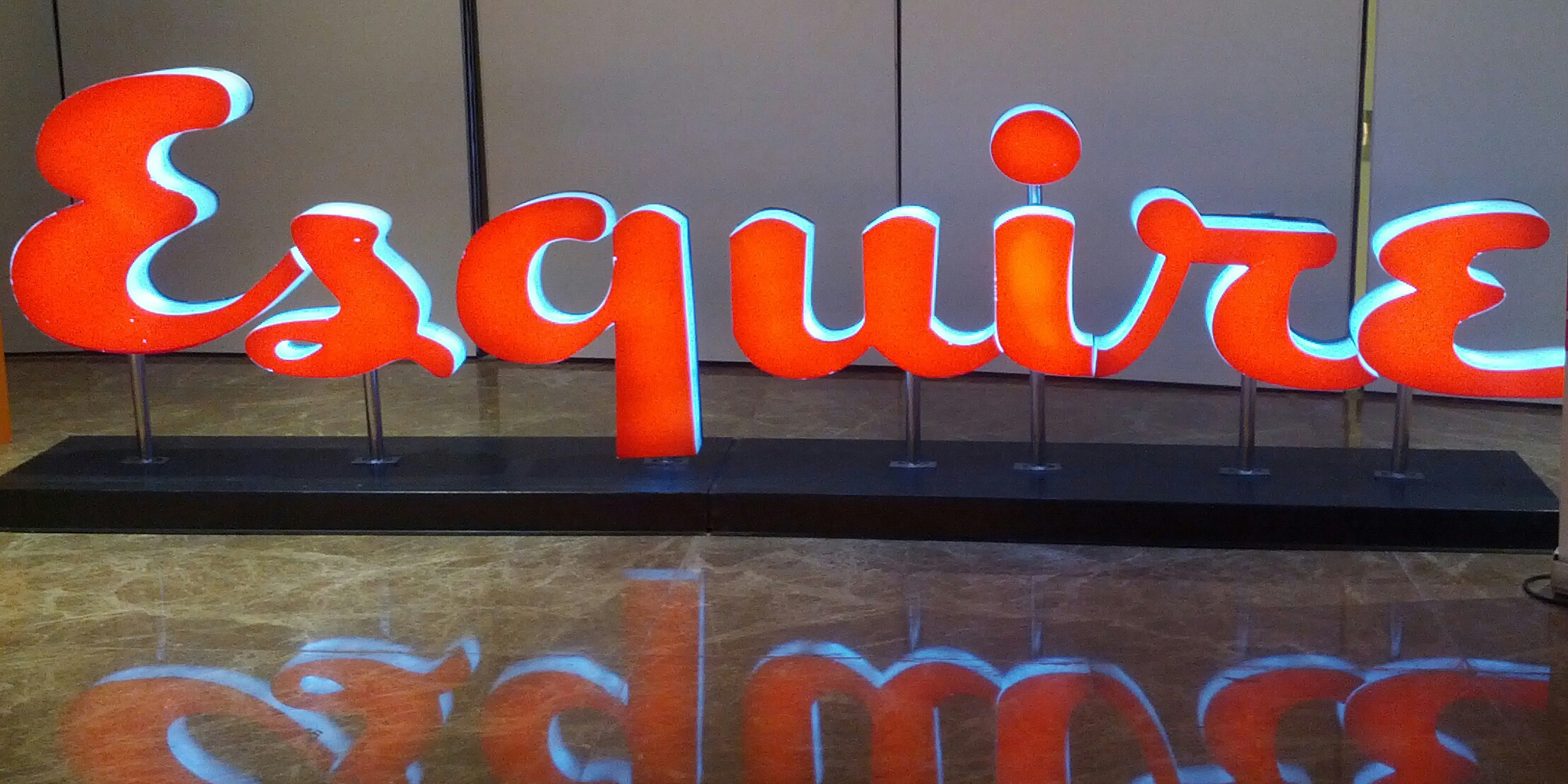 A red neon sign featuring Esquire's logo
