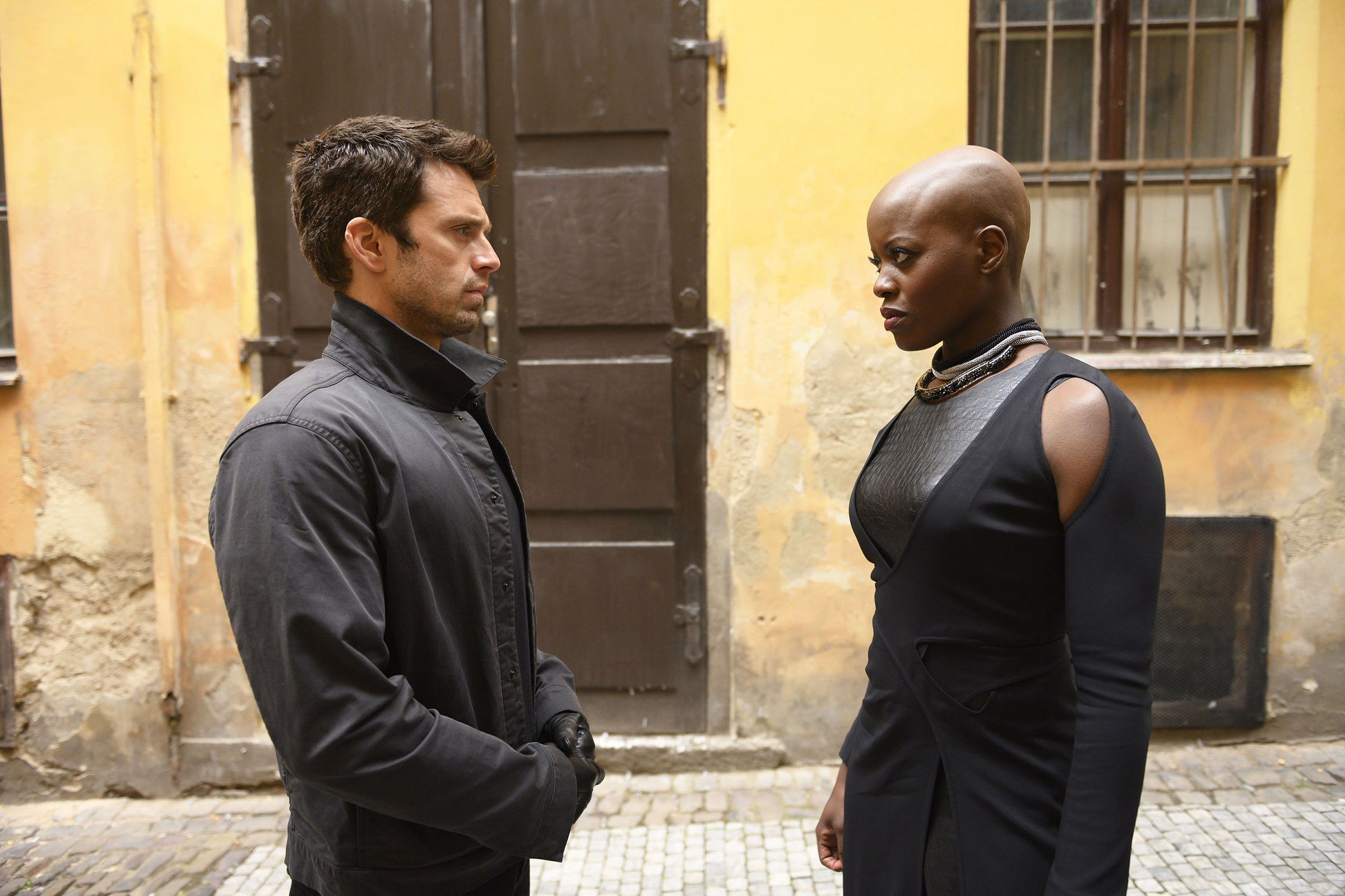 Bucky and Ayo stare intensely at each other while several feet apart. There is a dilapidated yellow building in the background.
