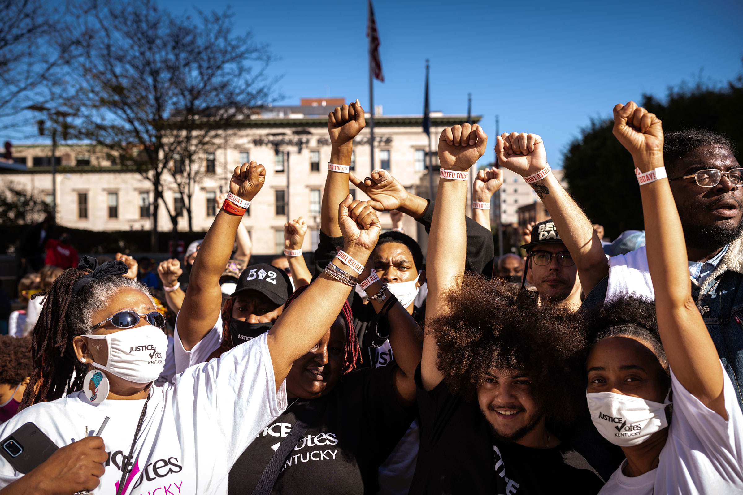 a group of Black protestors, who are all wearing masks, hold their fists up together after voting in Louisville, Kentucky