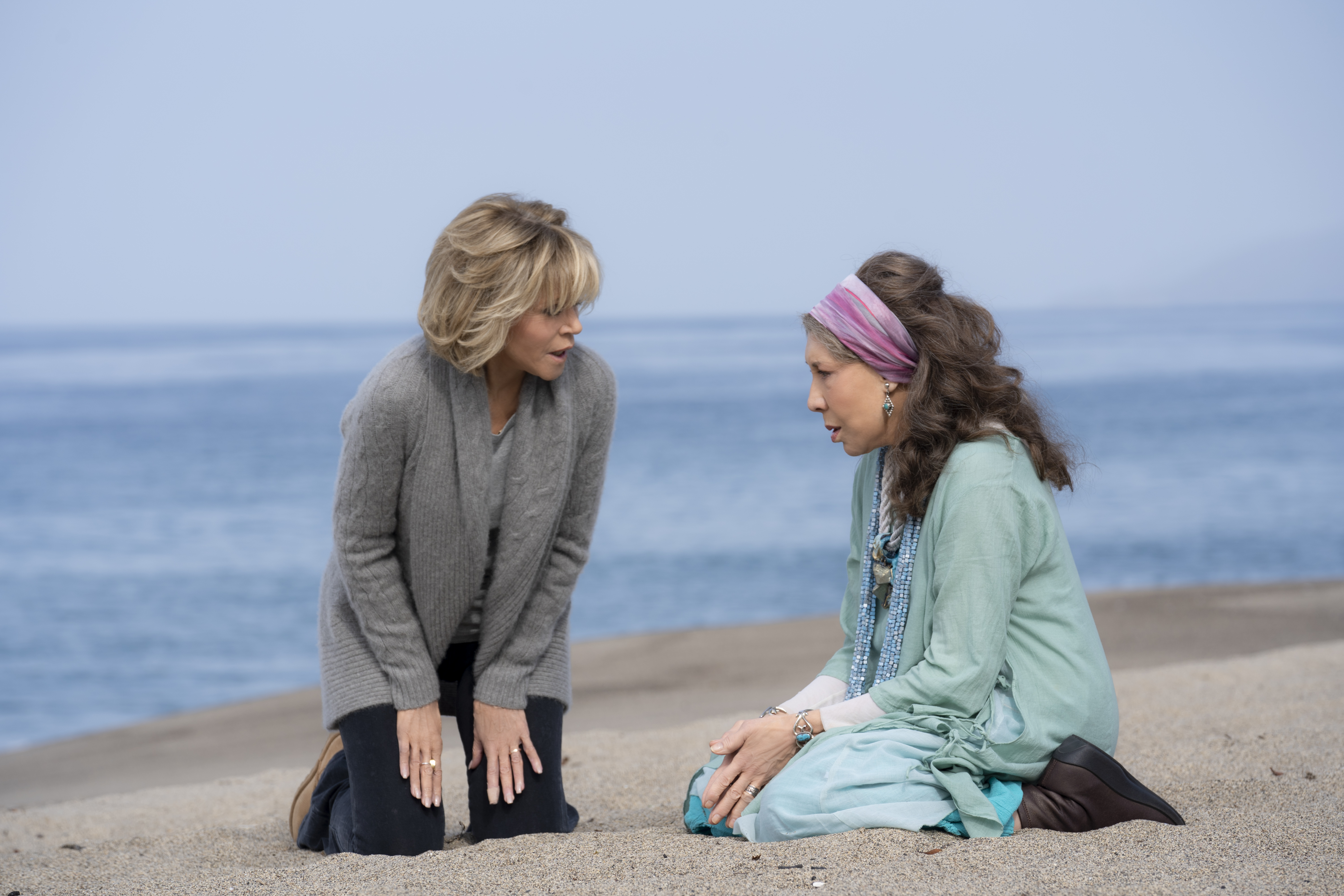 Grace and Frankie, two old white women, kneel on a beach