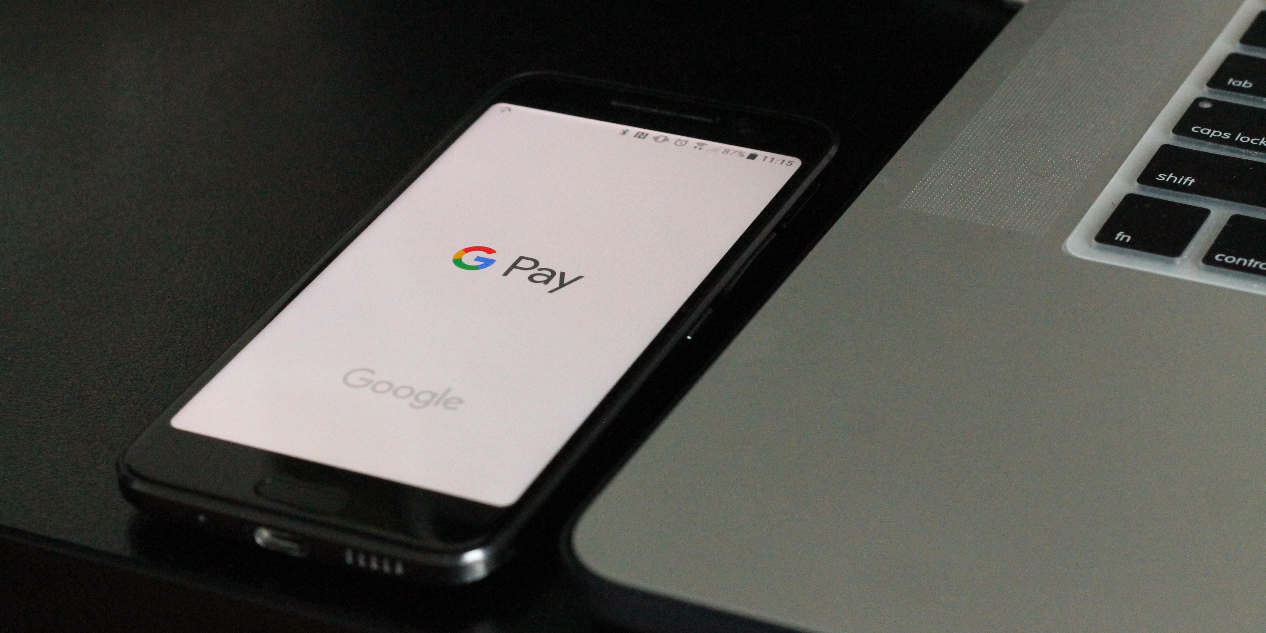 A black smart phone with the GPay app open next to a Macbook
