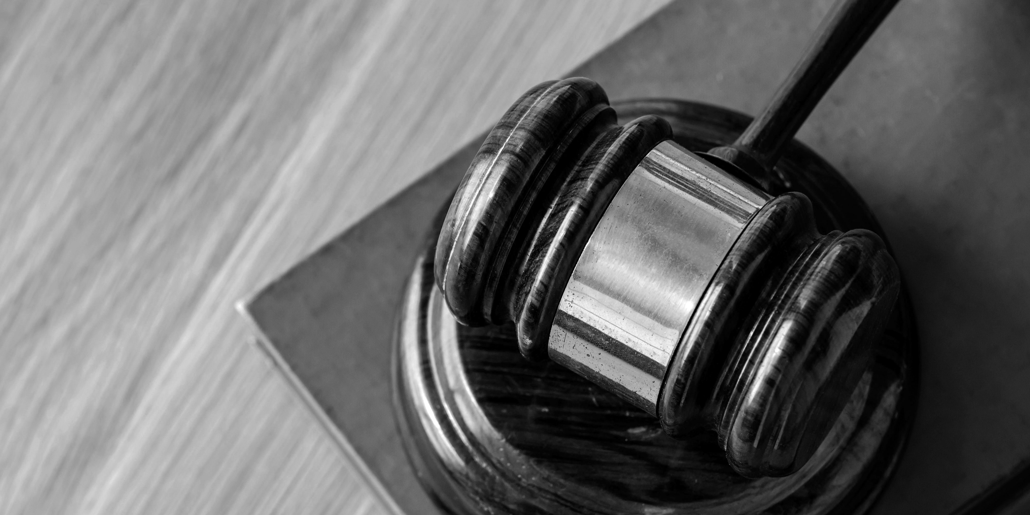 black and white image of a gavel laying on top of a wooden surface