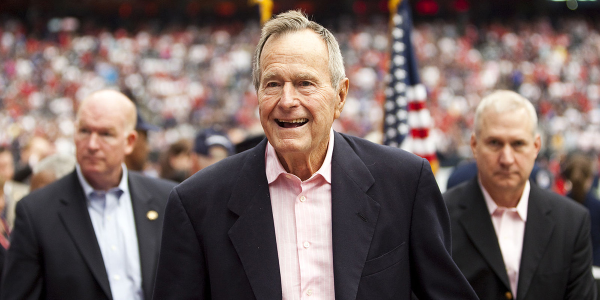 George H.W. Bush smiles, secret service agents and the crowd of a baseball stadium are in the background