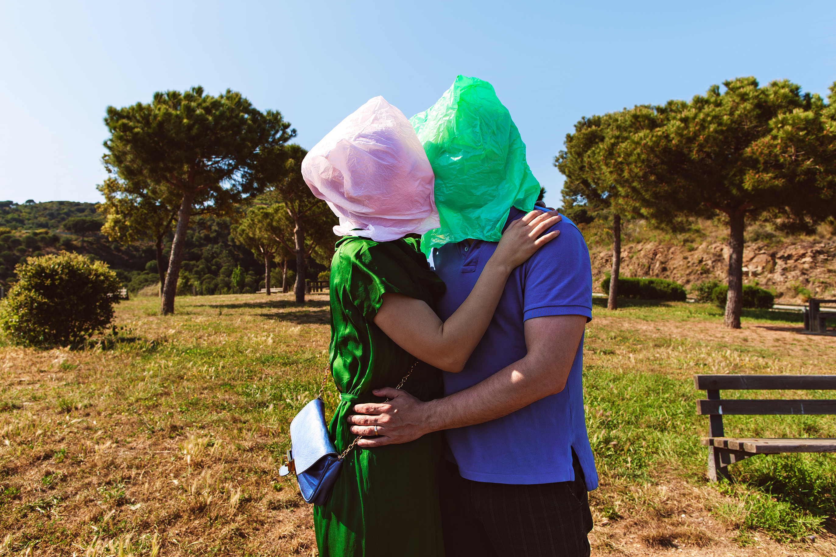 photo of a woman and man embracing and kissing in a field with colorful trash bags over their heads