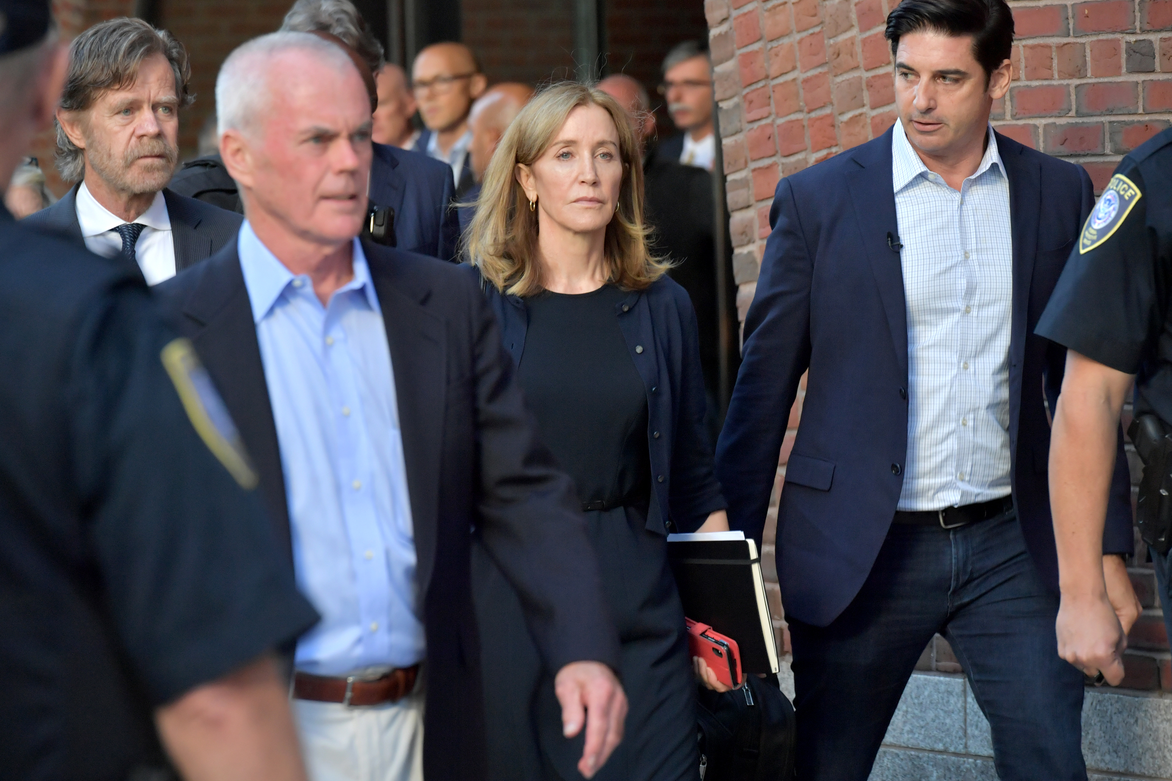 Felicity Huffman, a white woman, walks alongside security following her trial of the college admissions scandal.