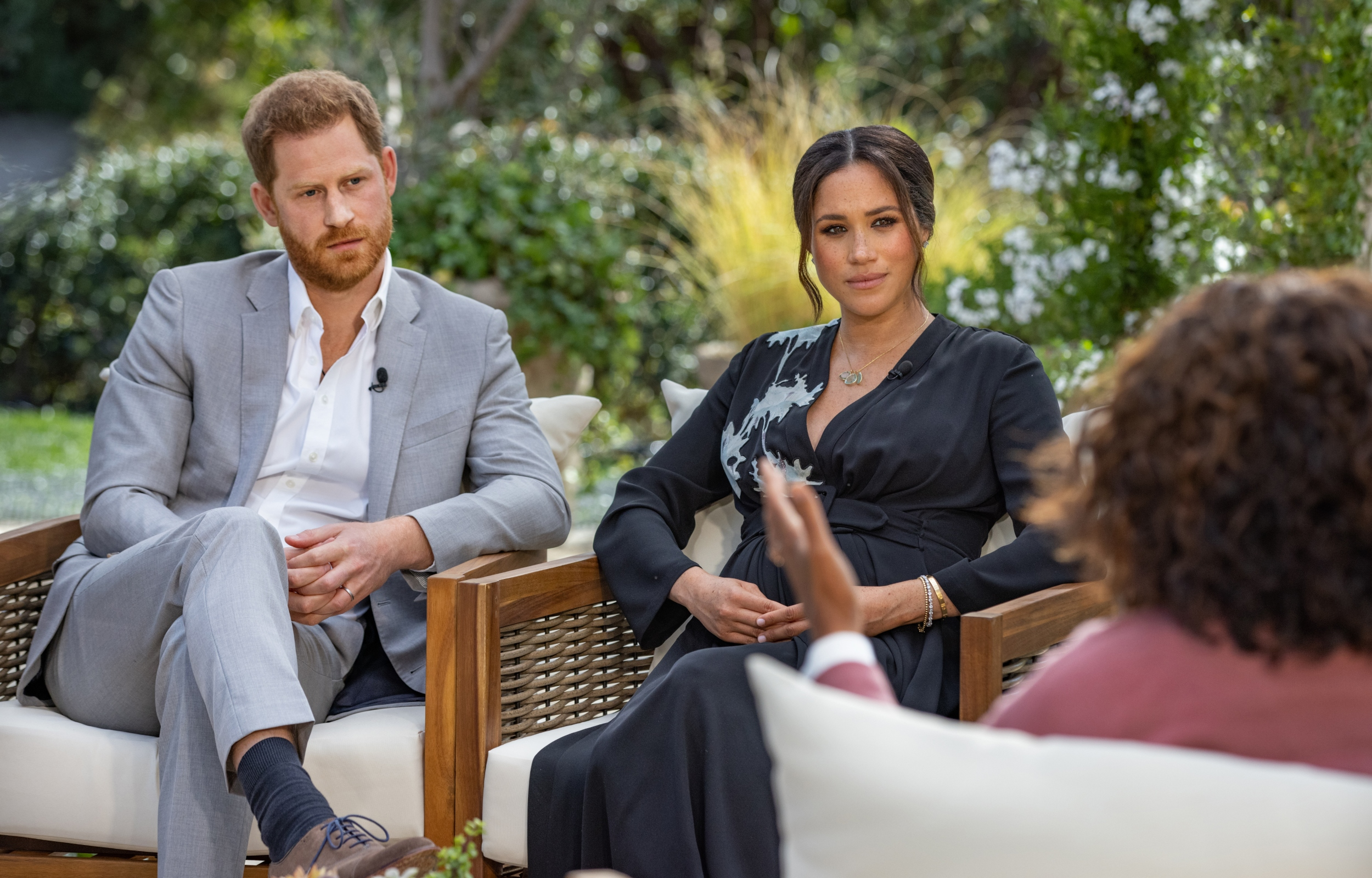 Oprah Winfrey interviews Prince Harry and Meghan Markle outside. Everyone is dressed up.