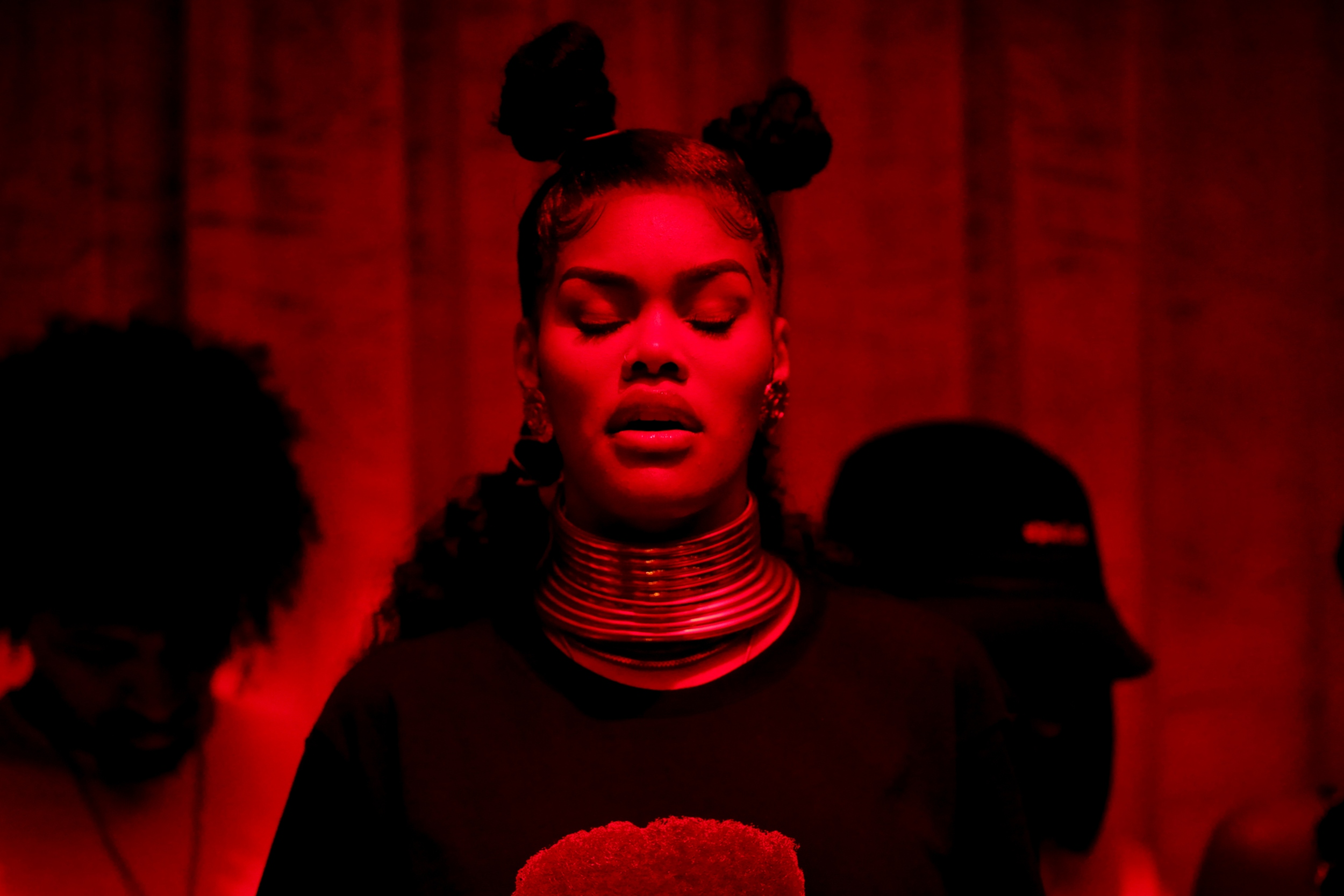 Teyana Taylor, a black woman, wears her hair in two buns and a large gold necklace. She is covered in a red light.