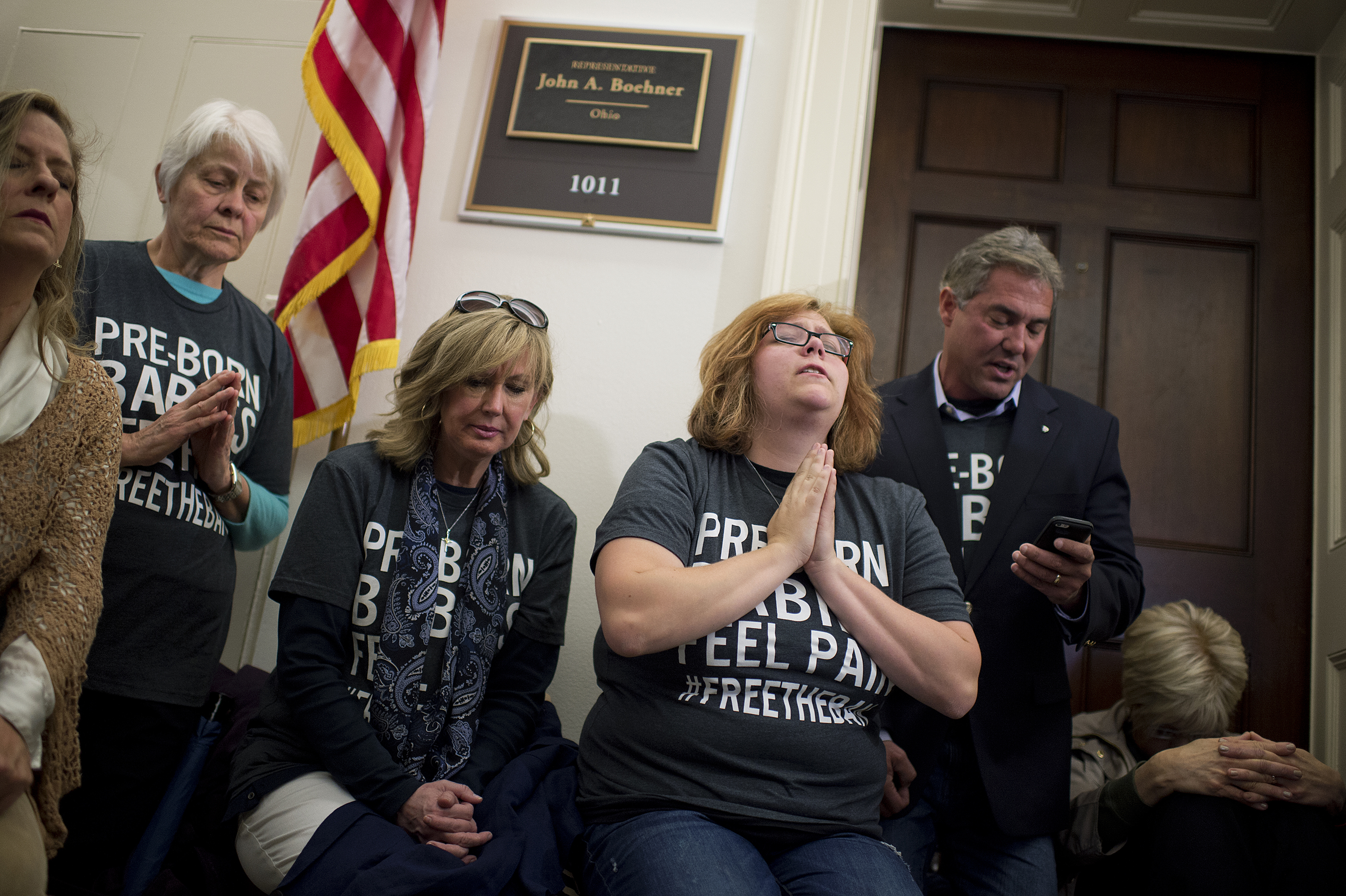 a white woman with black glasses closes her eyes and prays in front of a politician's office