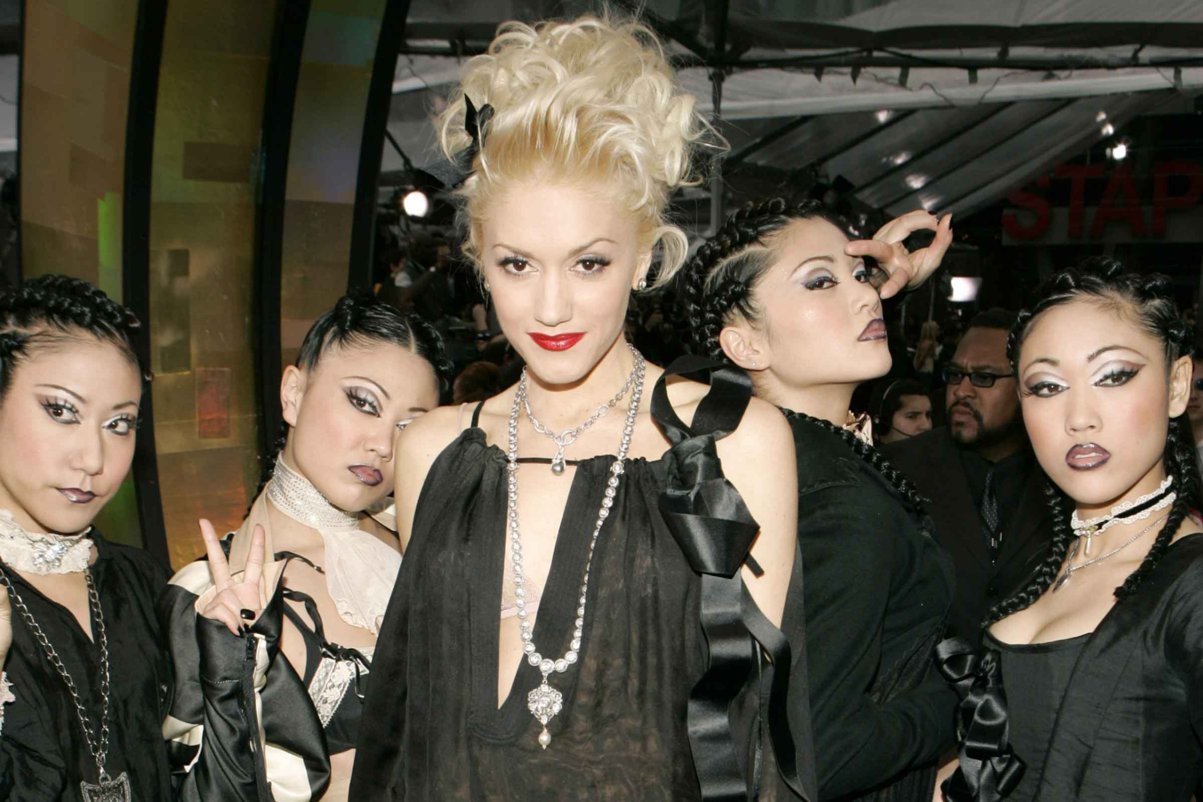 Gwen Stefani, a white woman with blond hair, poses alongside the Harajuku Girls, a group of four Japanese women dressed in all black