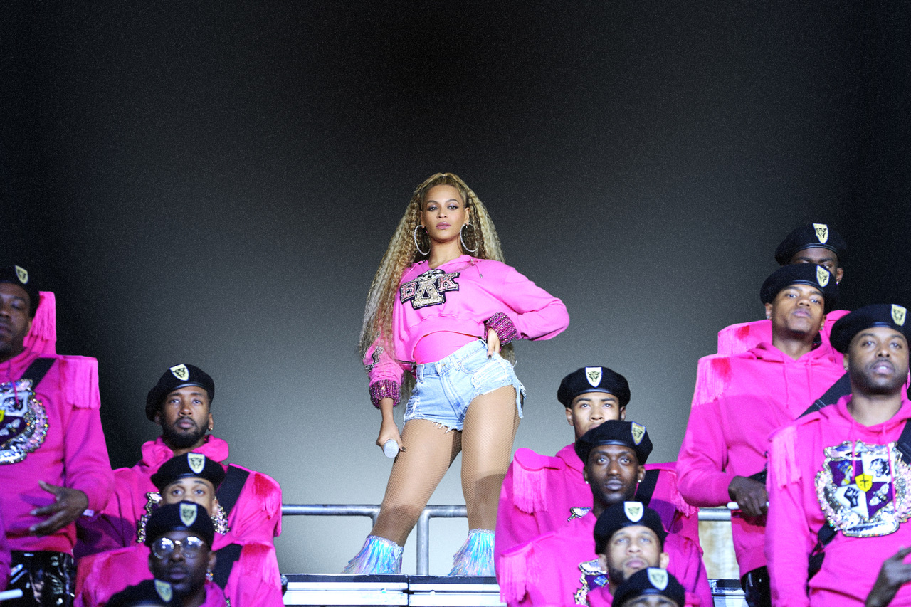 a lightskinned Black woman in a pink sweatshirt performs on a stage with a band