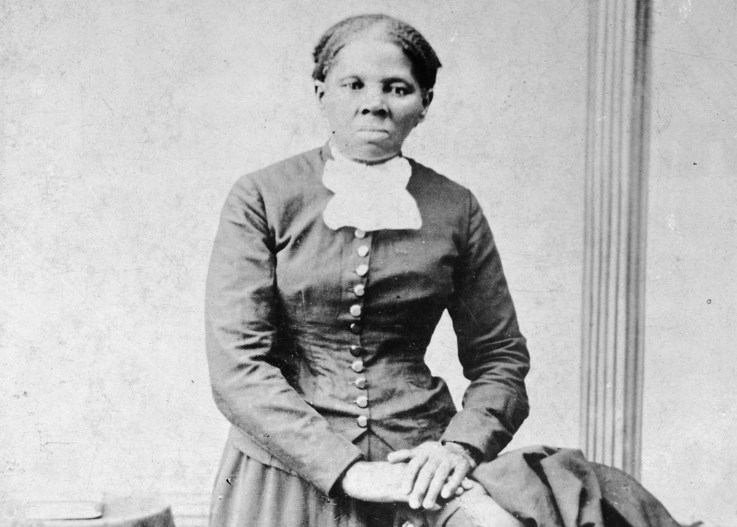 an old photo of a Black woman wearing a black tuxedo jacket with a white tie