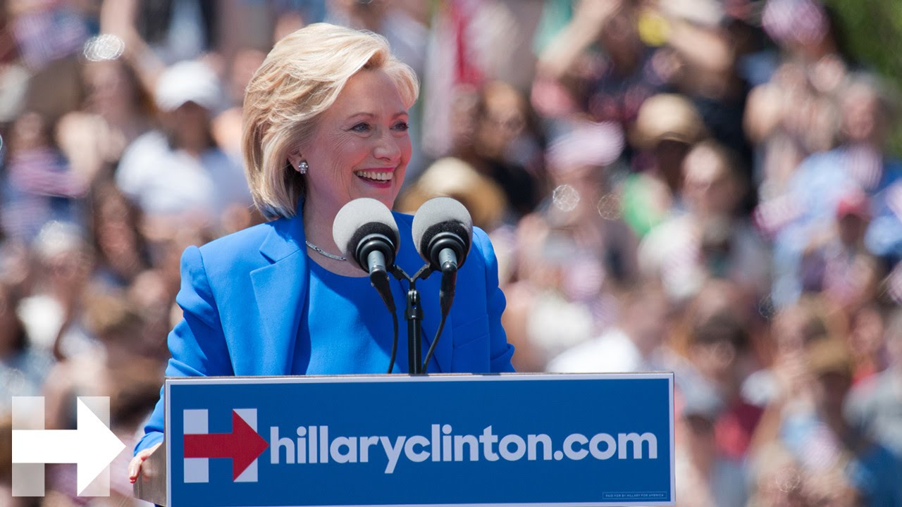 a white woman with short, blond hair wears a blue suit and stands behind a podium