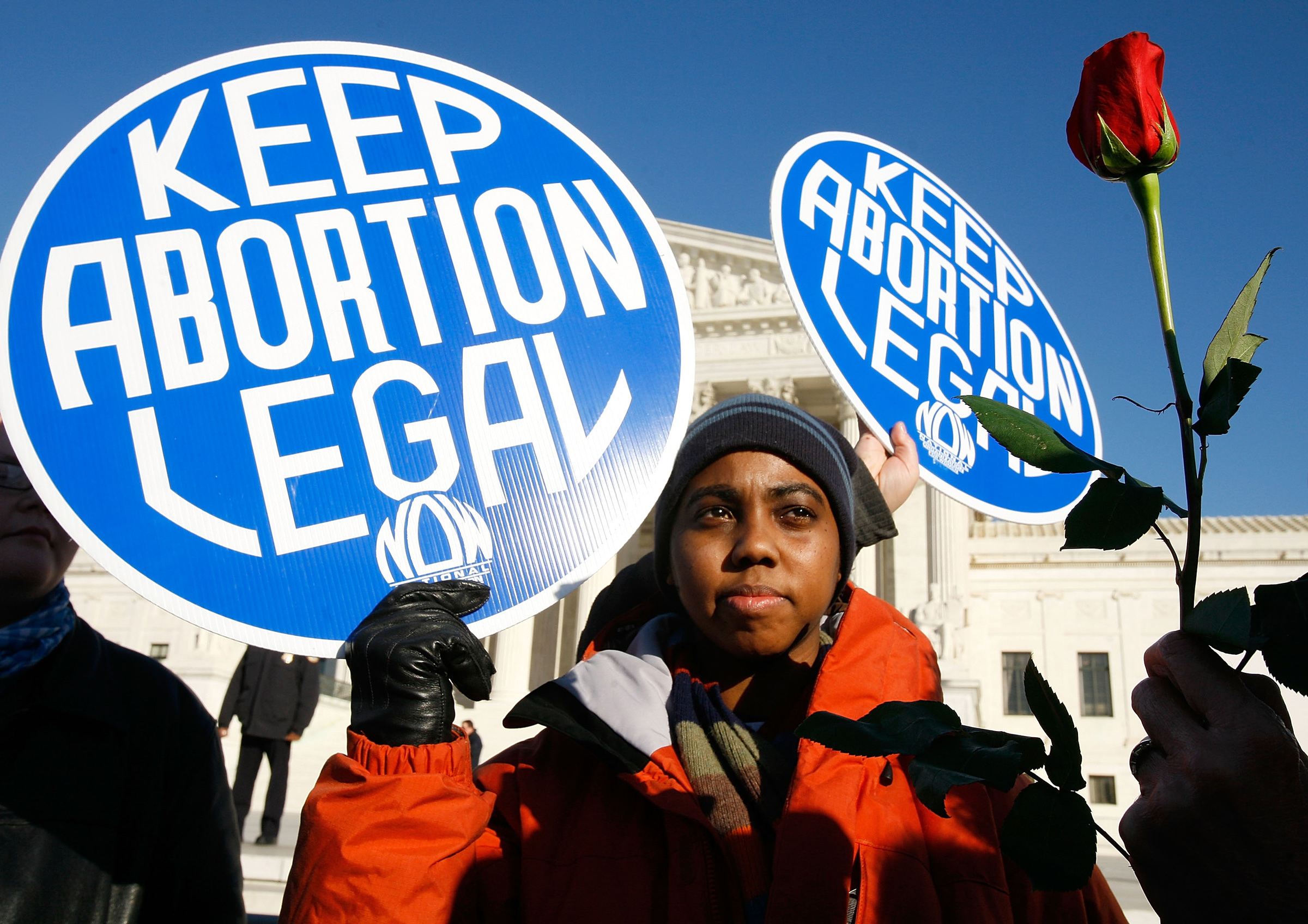 a Black person wearing all blue holds a blue Keep Abortion Legal sign in front of a stone building