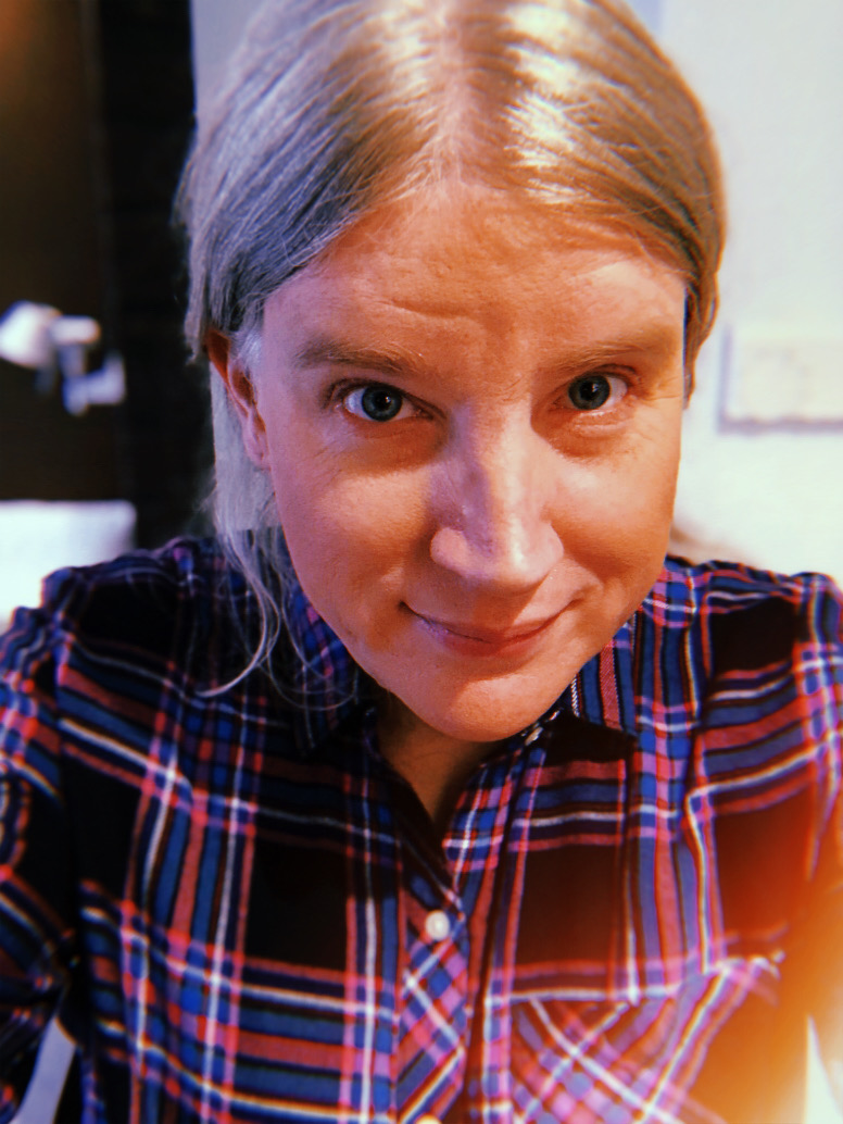 Carolyn Petit, a white person with blond hair in the ponytail, takes a selfie