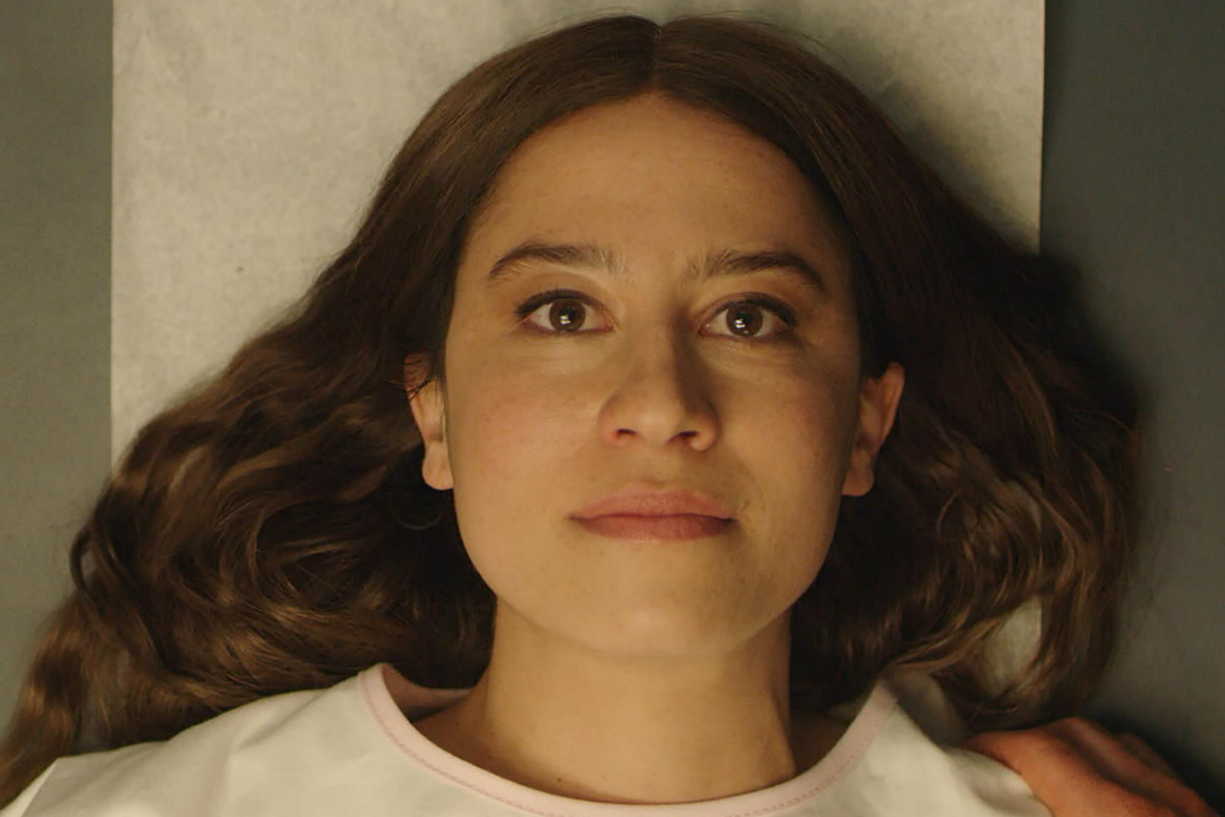 Ilana Glazer plays Rose, a white woman with short brown hair, who is lying on her back in a hospital gown on an exam table