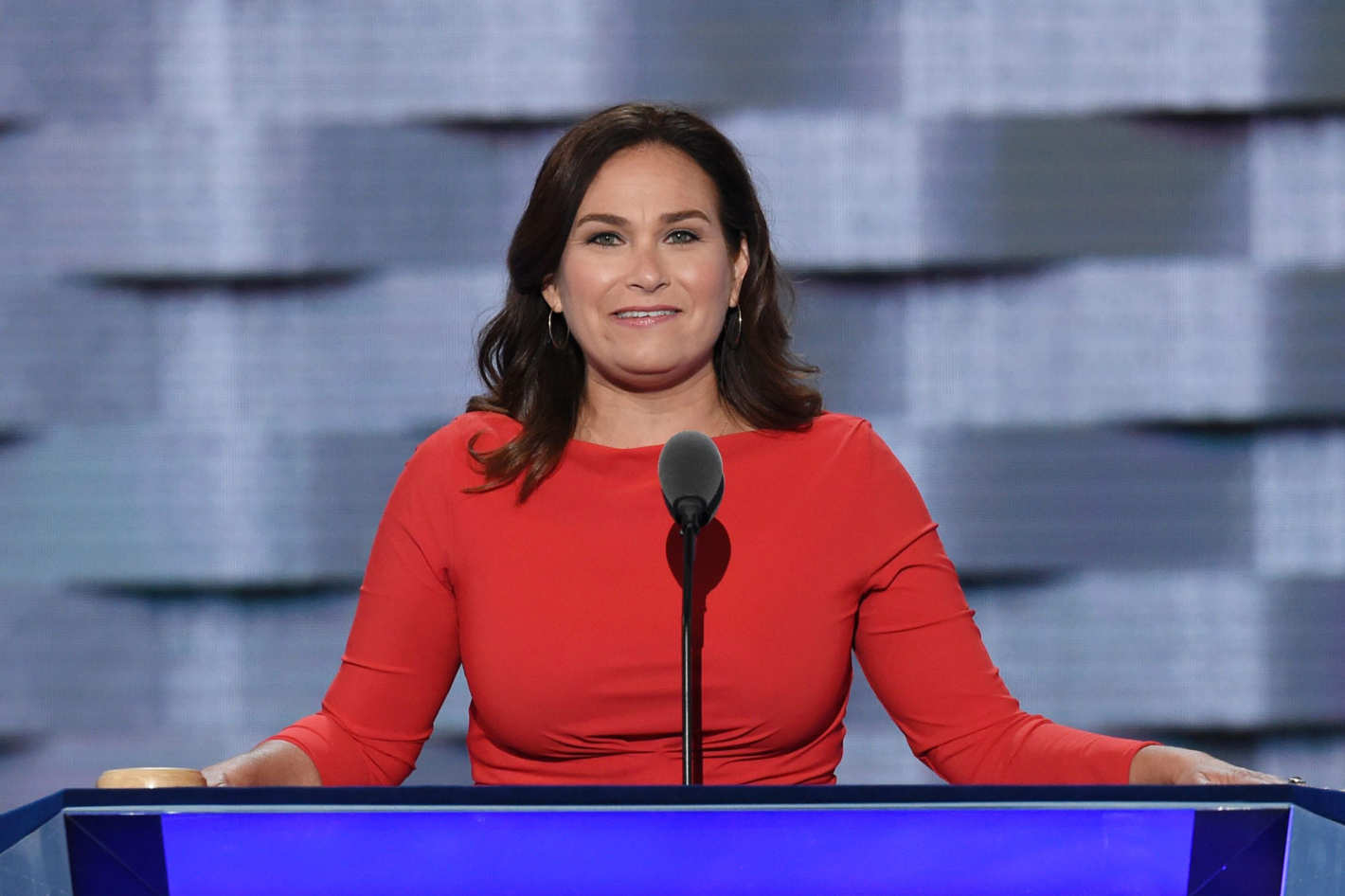 a white woman with brown hair speaks behind a red podium