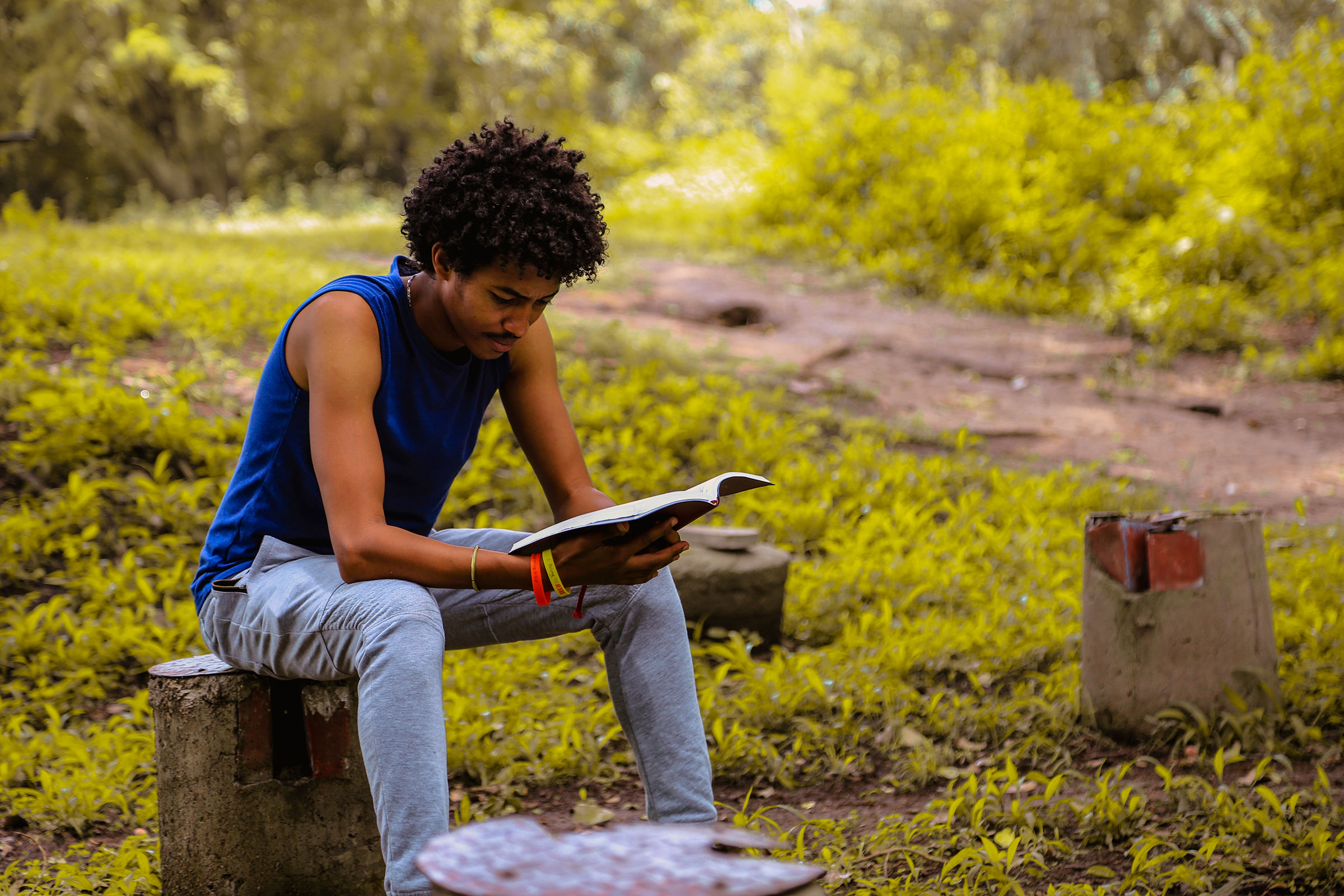 a Black man with short, black hair, and a blue shirt sits on a concrete bence reading a book