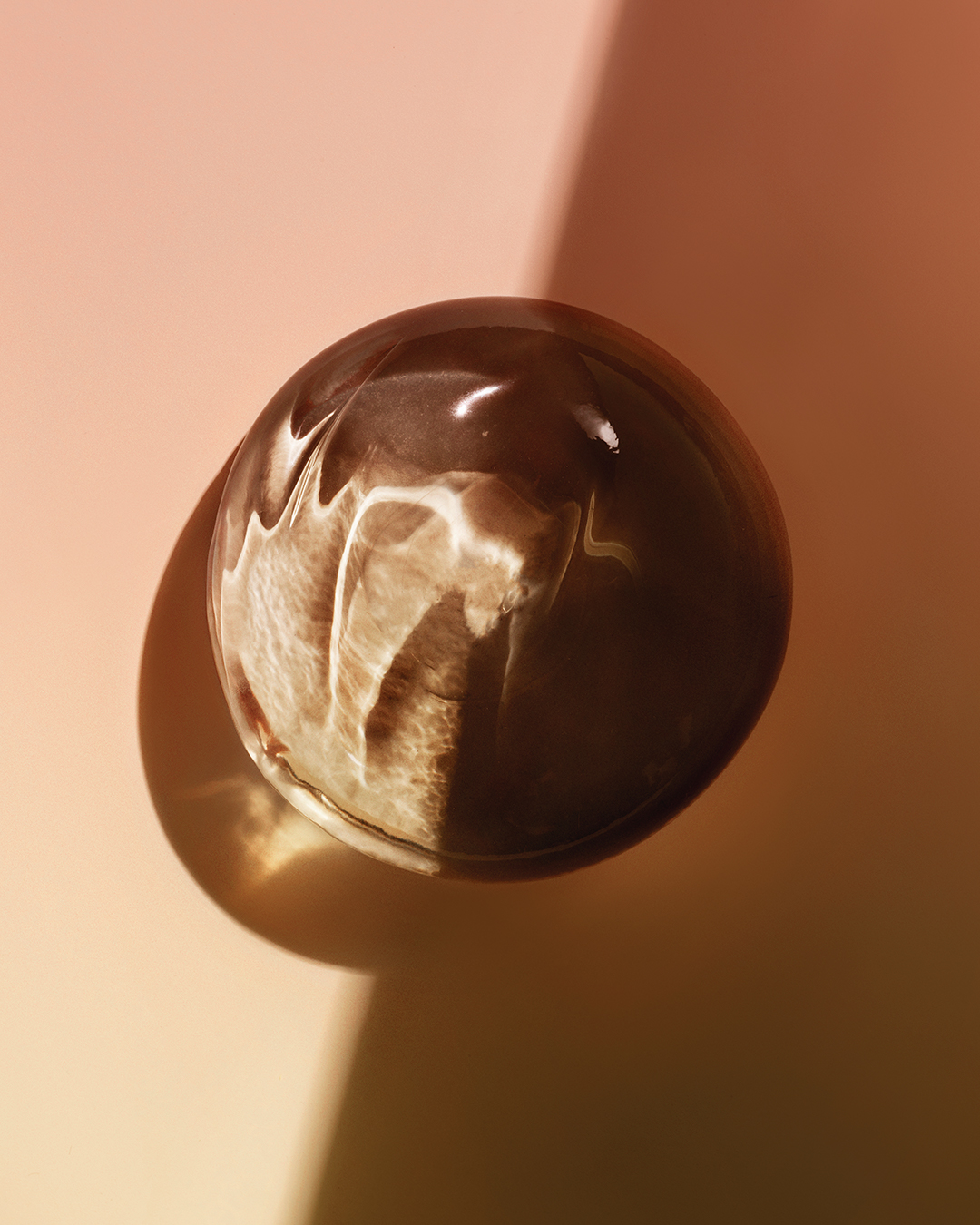image of a silicone breast implant against a brown background