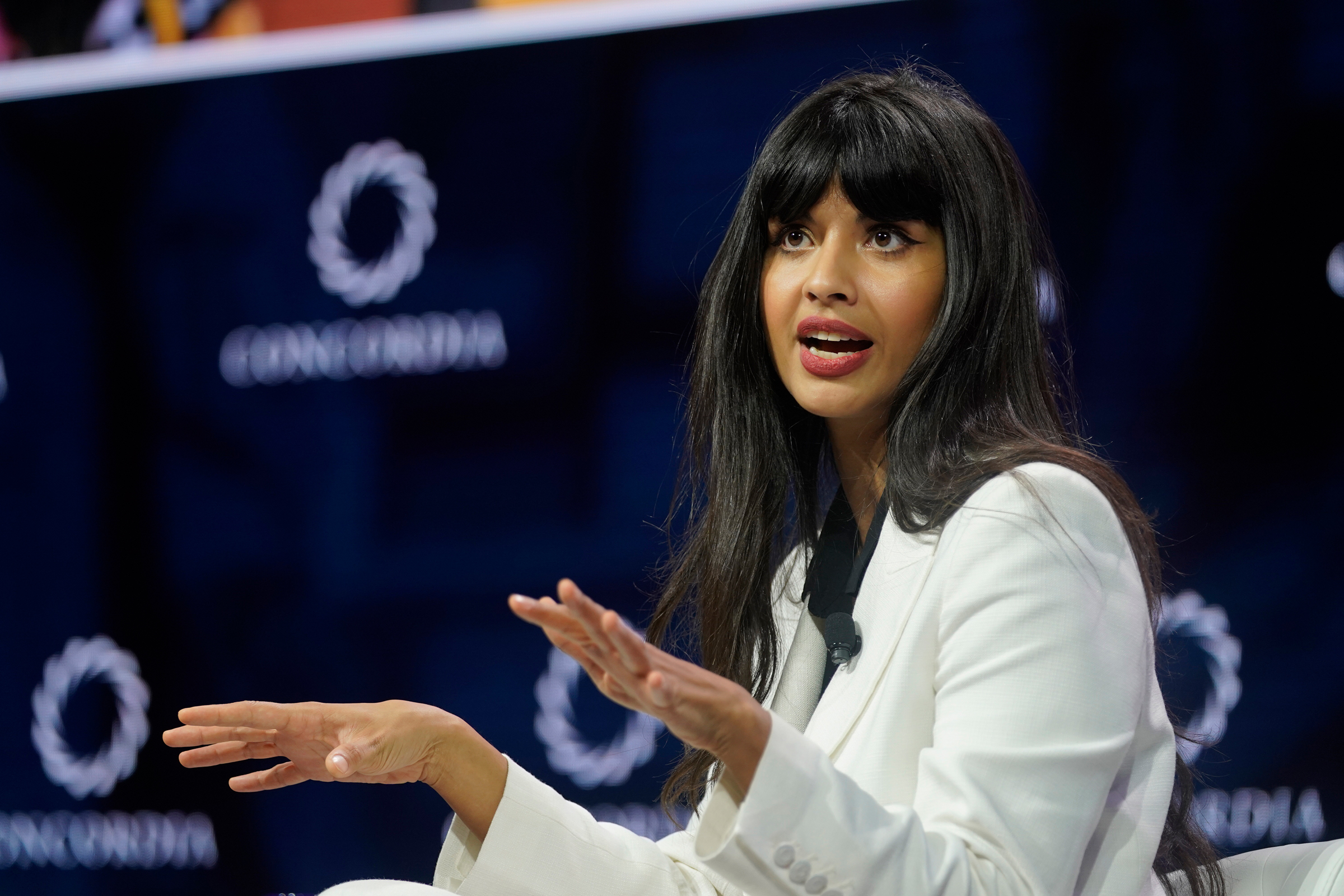 Jameela Jamil, a British Indian woman, looks off camera mid sentence. Her arms are raised suggesting passionate speech.