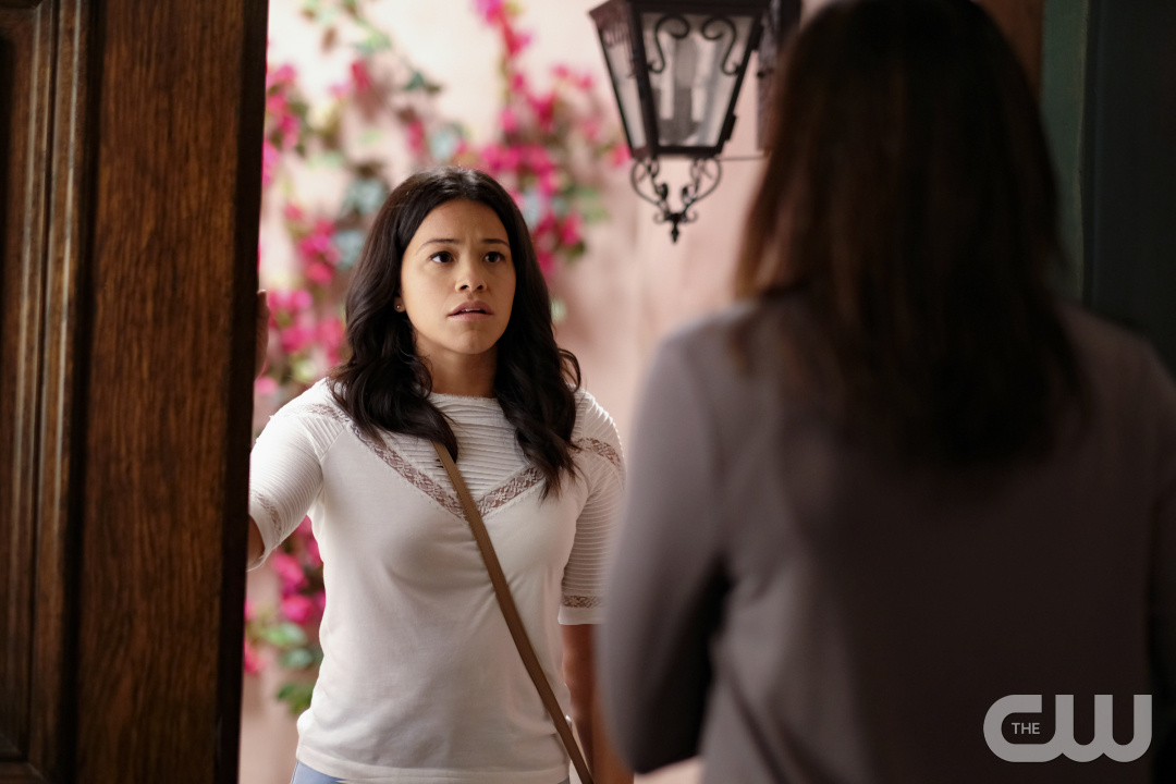 Gina Rodriguez, a Latinx woman with dark brown hair, stares at some standing in the doorway on Jane the Virgin