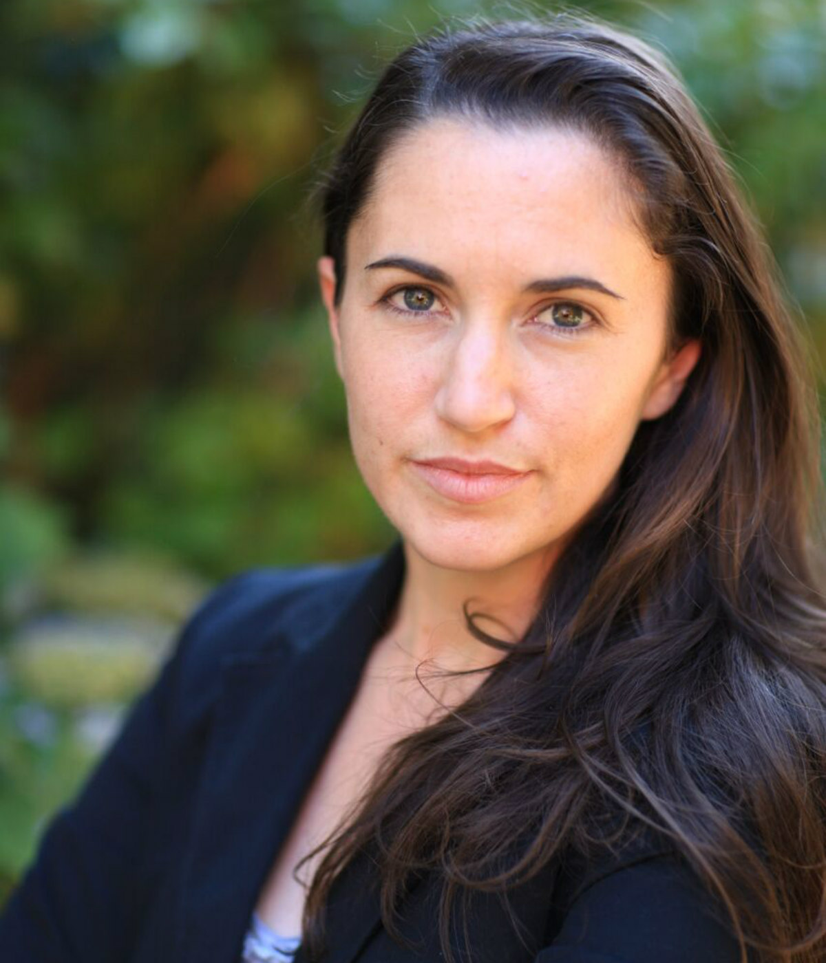 Jenara Nerenberg, a white person with shoulder-length brown hair, stares at the camera