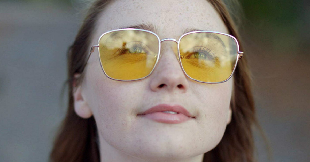 a young, white woman wearing yellow sunglasses looks at the sky