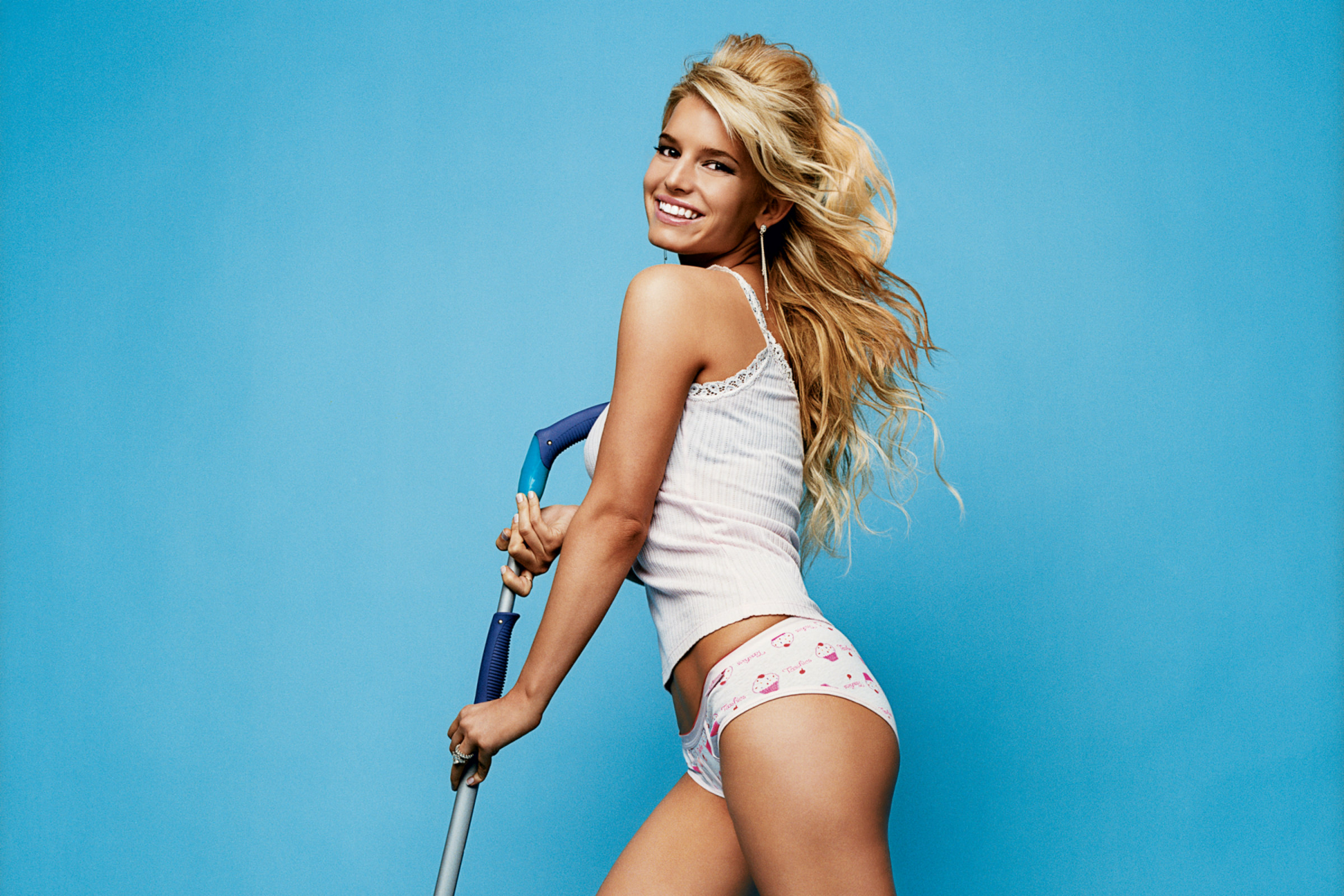 Jessica Simpson, a thin white woman with curly, blond hair, holds a mop against a light-blue background while wearing a thin white t-shirt