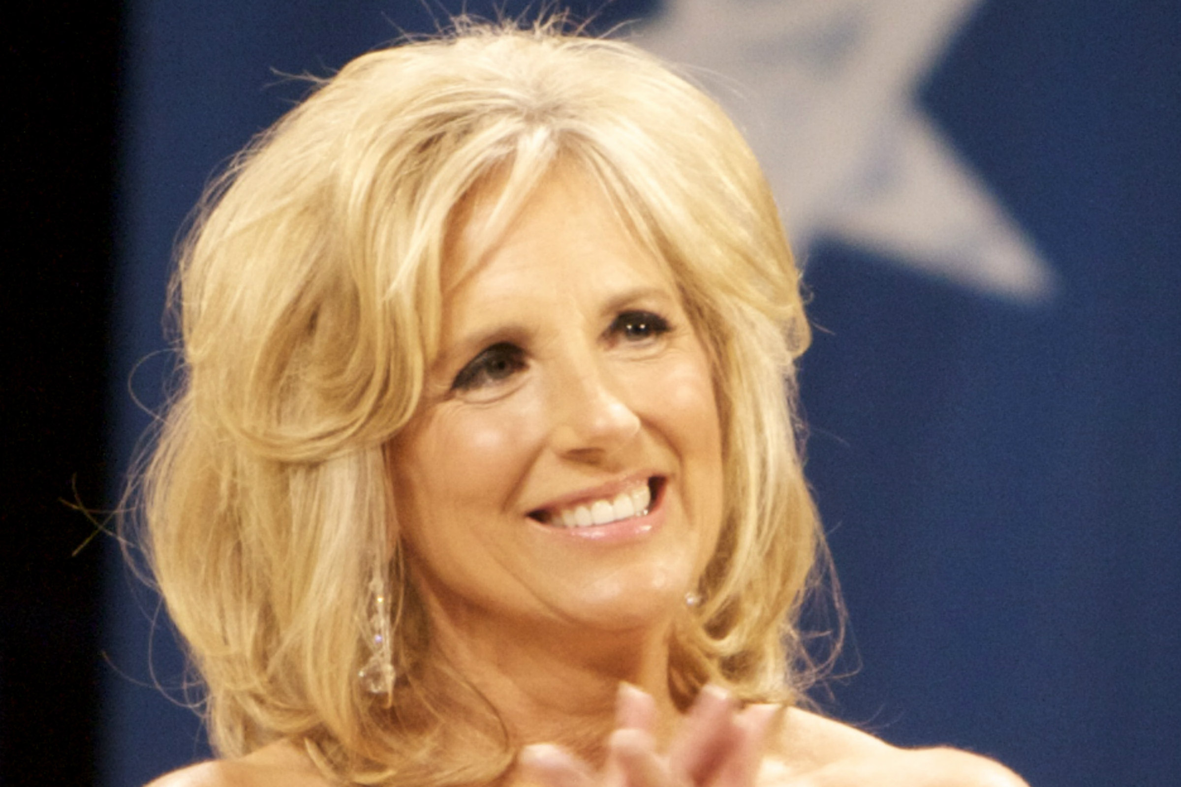 Jill Biden, an aging white woman with shoulder-length blond hair, smiles while wearing a red gown at the 2009 Inaugural Ball