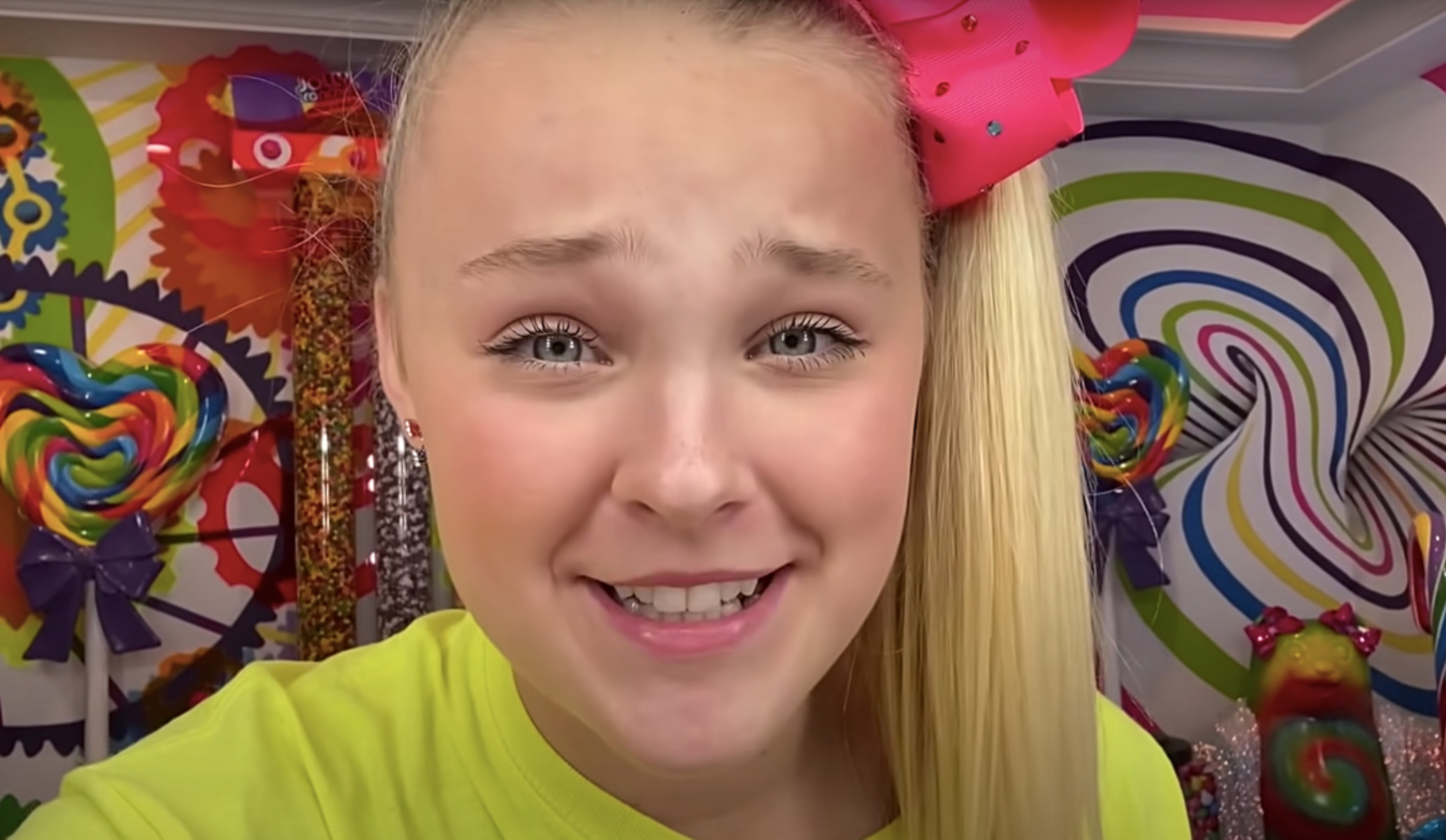 JoJo Siwa, a white teen girl, has her blond hair in a high ponytail and bow on the top of her head. She holds the camera close to her face for a selfie video.