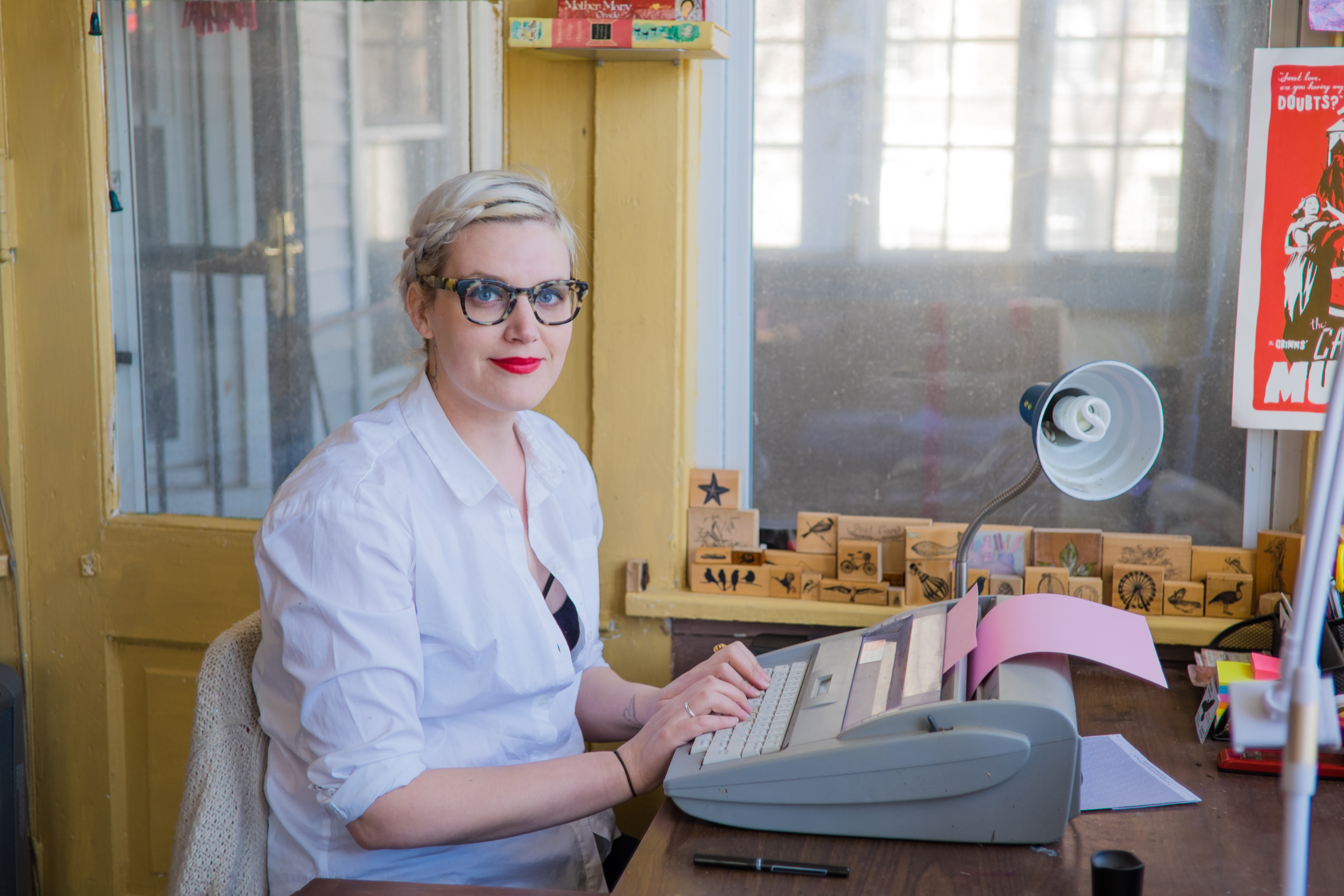 white woman with short platinum blonde hair and leopard print glasses sitting in front of a typewriter with pink paper in front of it on a wooden desk