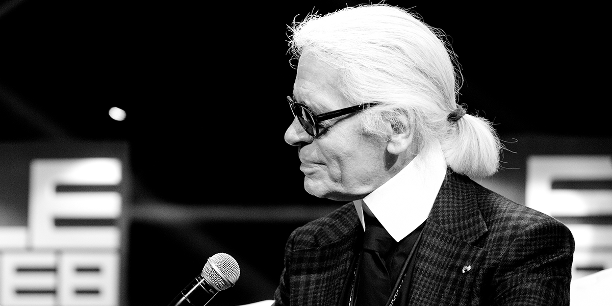 A black and white photo of an elderly man wearing black sunglasses and long white hair tied back into a ponytail is smiling on stage