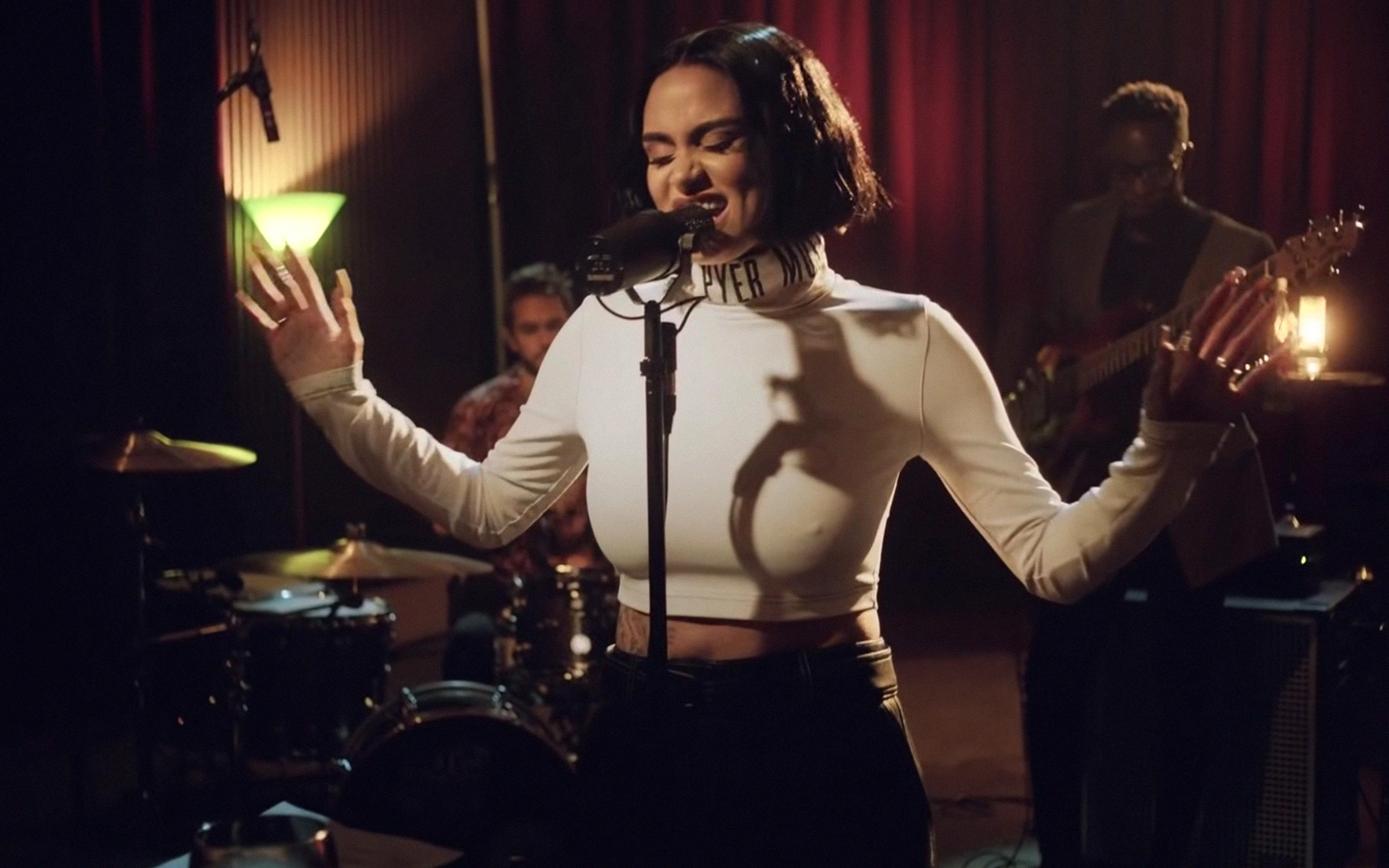 Kehlani, a light skinned Black woman, has short black hair parted down the center. She sings on stage while wearing a white turtleneck.