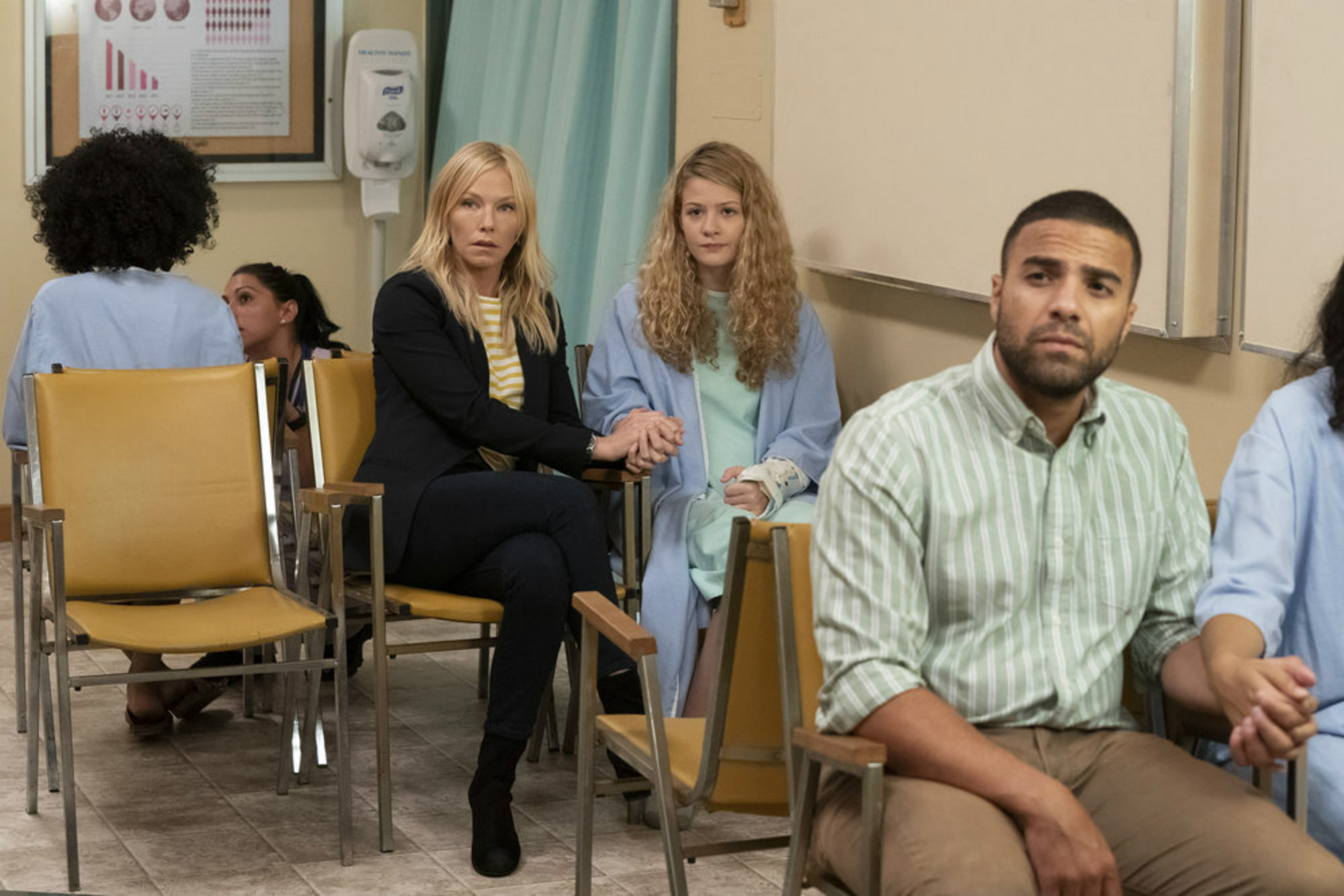 Kelli Giddish, a white woman police detective on Law & Order: SVU, sits besides a white teenager in a hospital room