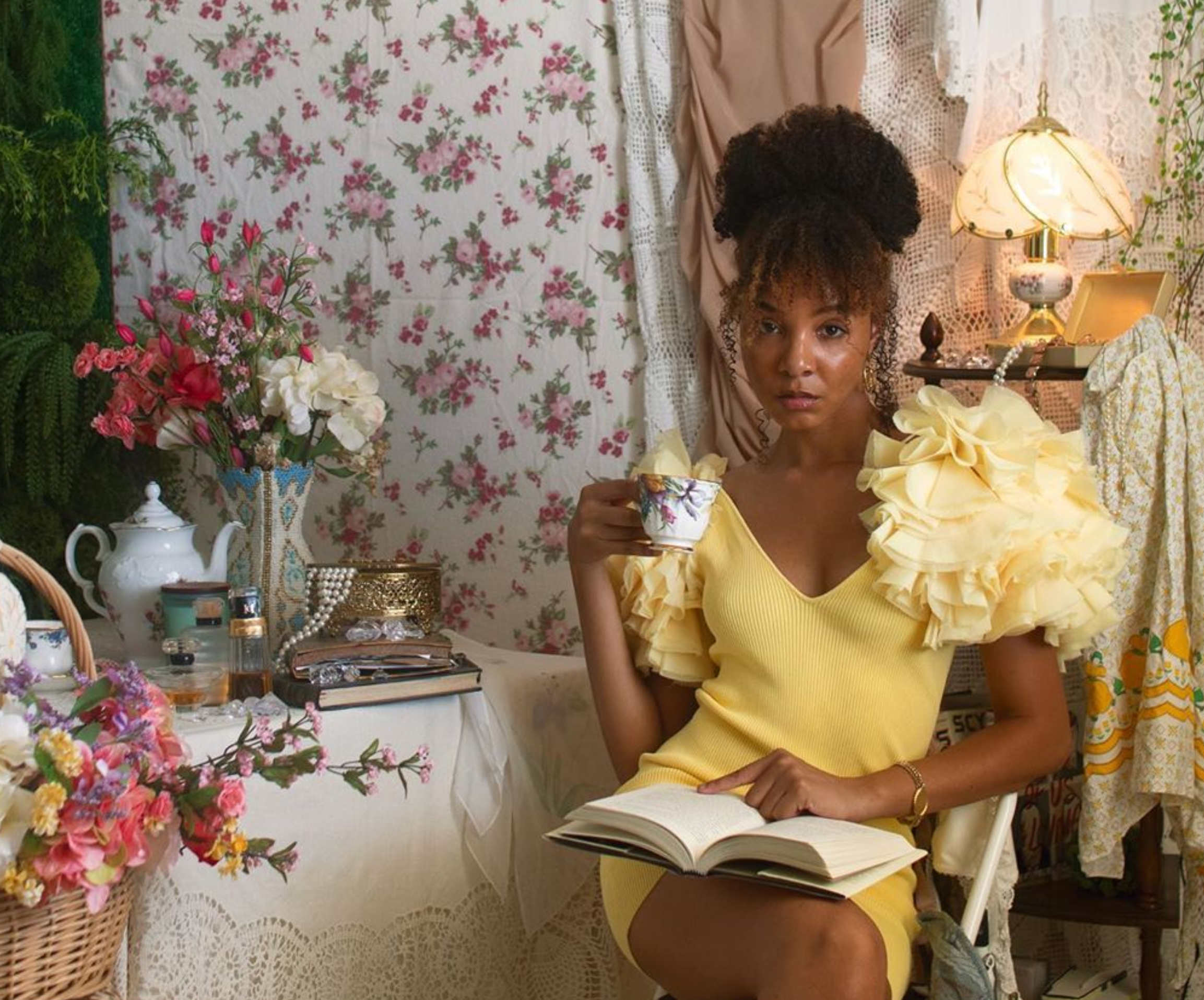 Kimberly Douglas, a Black woman, wears a dainty yellow dress and is surrounded by various soft fabrics. She sits at a table with a white tea set and holds a tea cup.