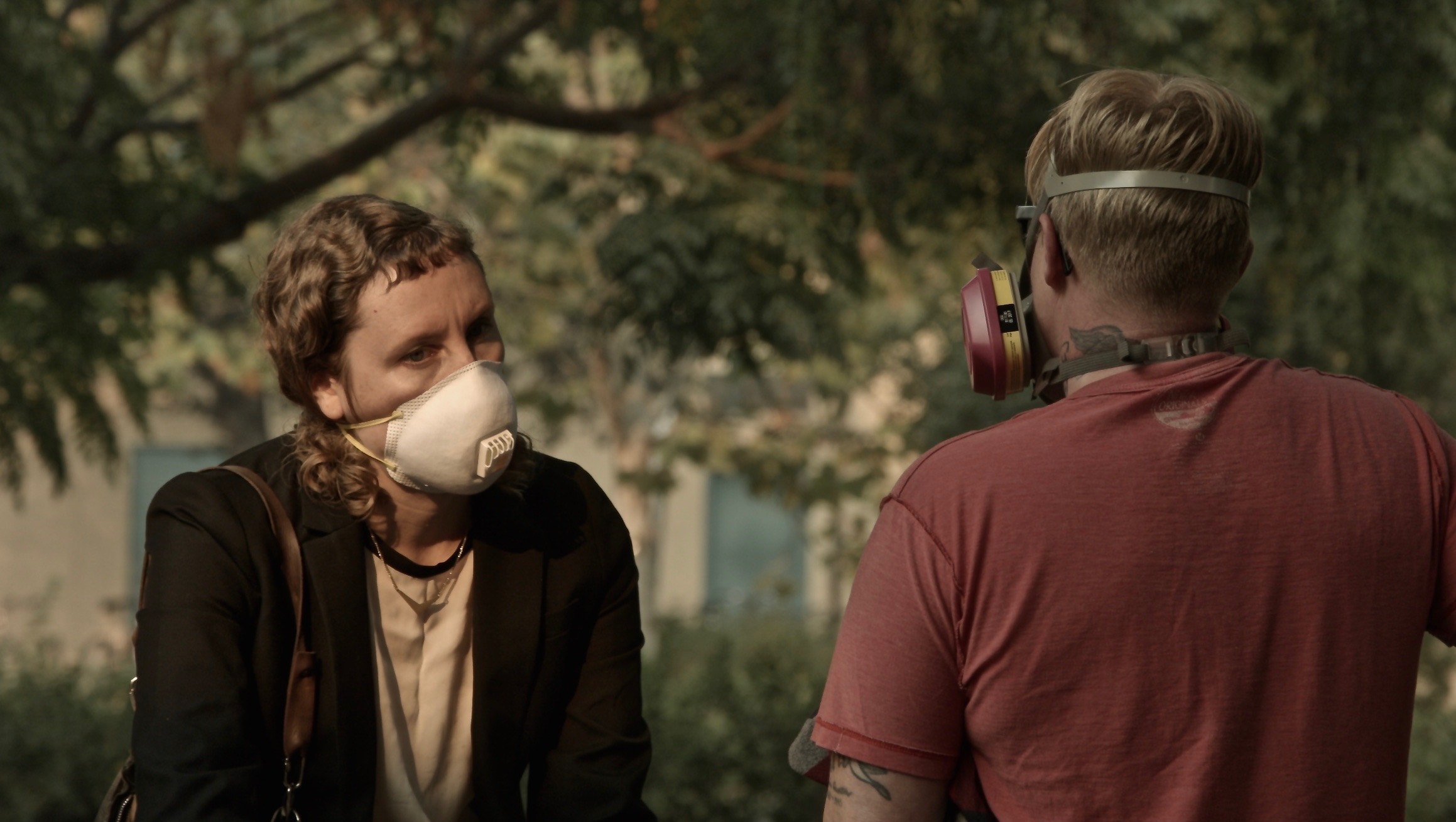 a white woman with brown hair and wearing a mask over her mouth looking at a white person with blonde hair who's also wearing a gas mask