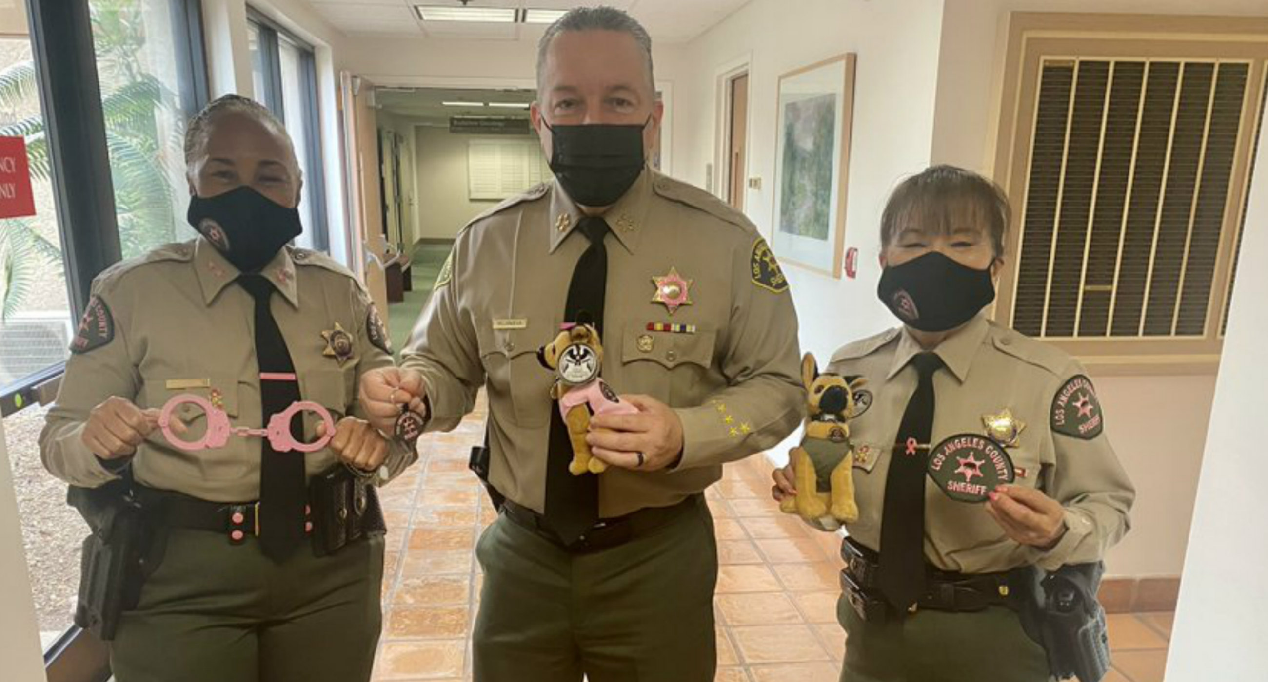 L.A. County Sheriff Alex Villanueva, a Latinx man in a brown uniform, poses alongside two women officers in brown uniforms as they all hold pink handcuffs